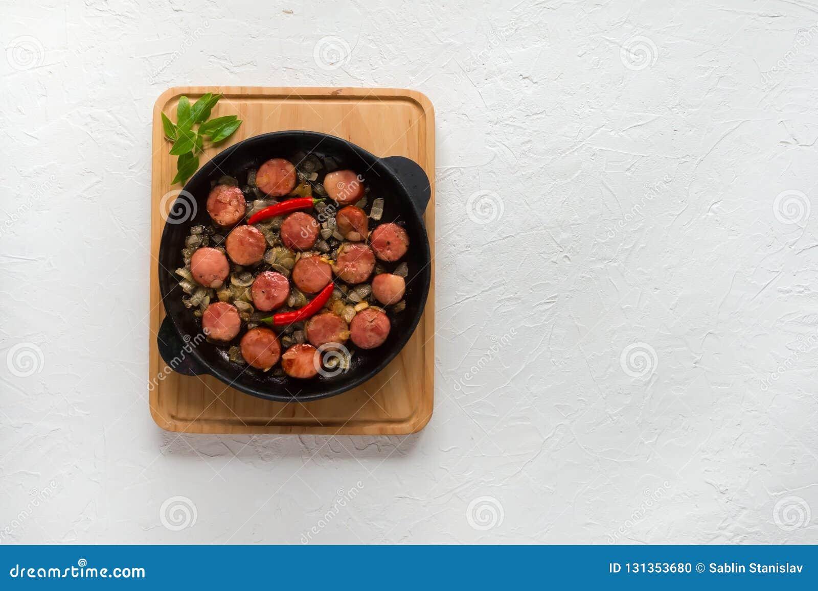 Apetyczni kawałki smażąca kiełbasa z cebulami na porcji niecce Odgórny widok