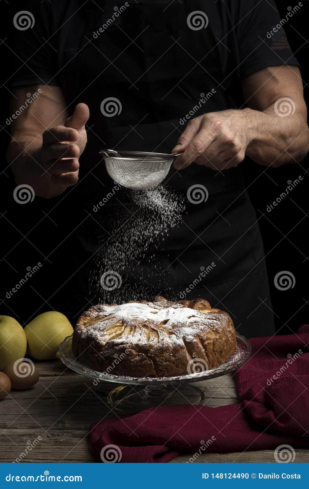 Apfelkuchen mit Puderzucker auf dunklem Hintergrund und Mann im Schutzblech