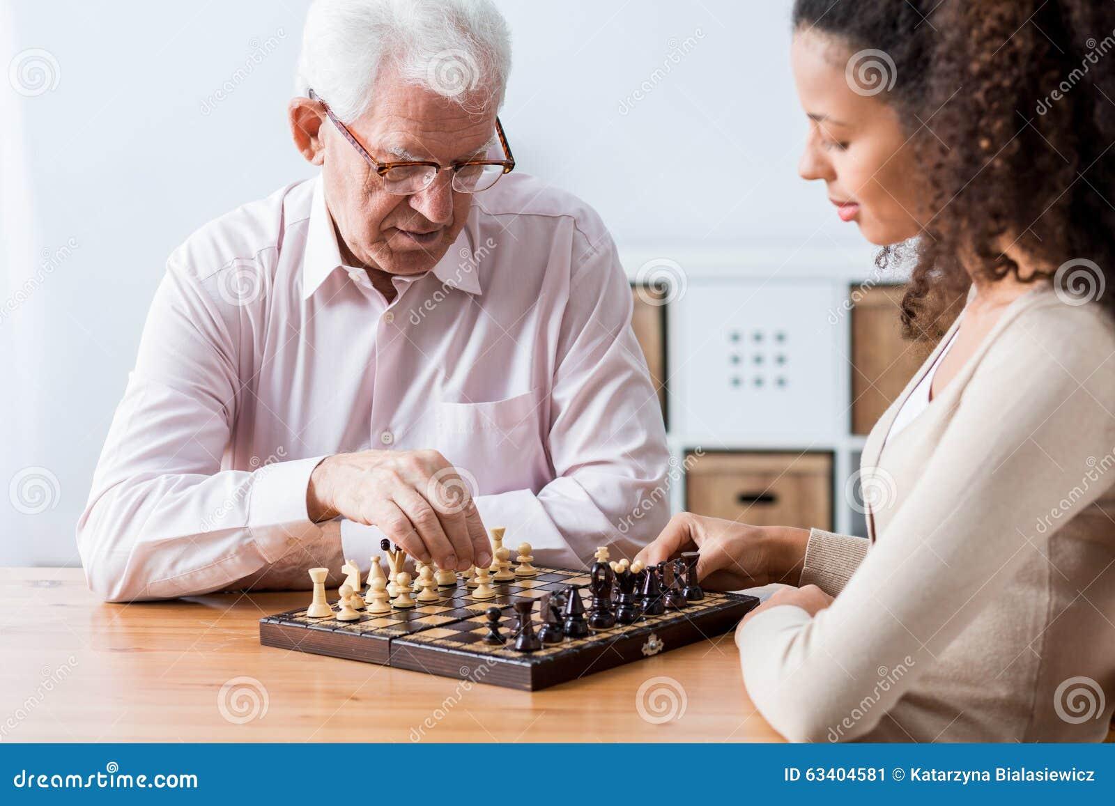 Aposentado e cuidador que jogam a xadrez