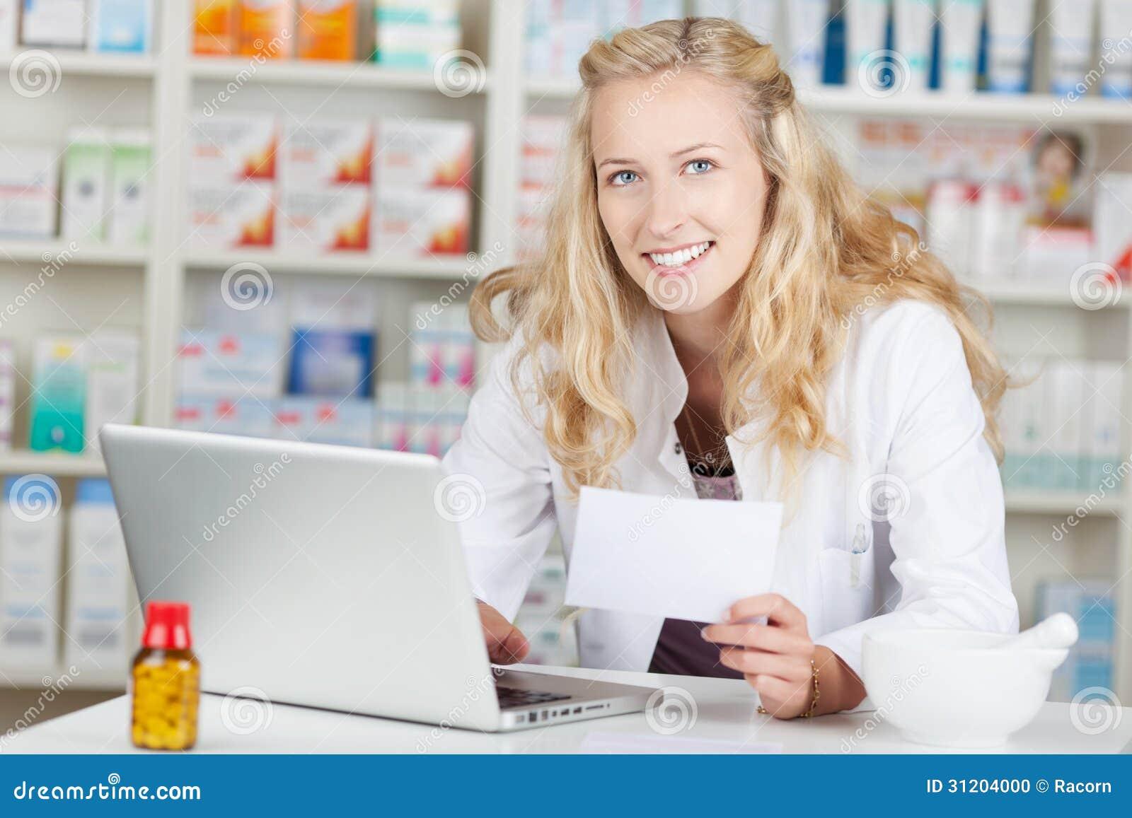 Apotekare Holding Prescription Paper, medan genom att använda bärbara datorn på Coun