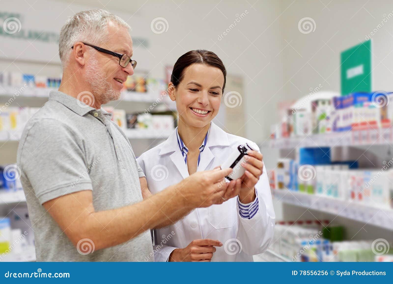 Apotheker, der dem älteren Mann Droge an der Apotheke zeigt