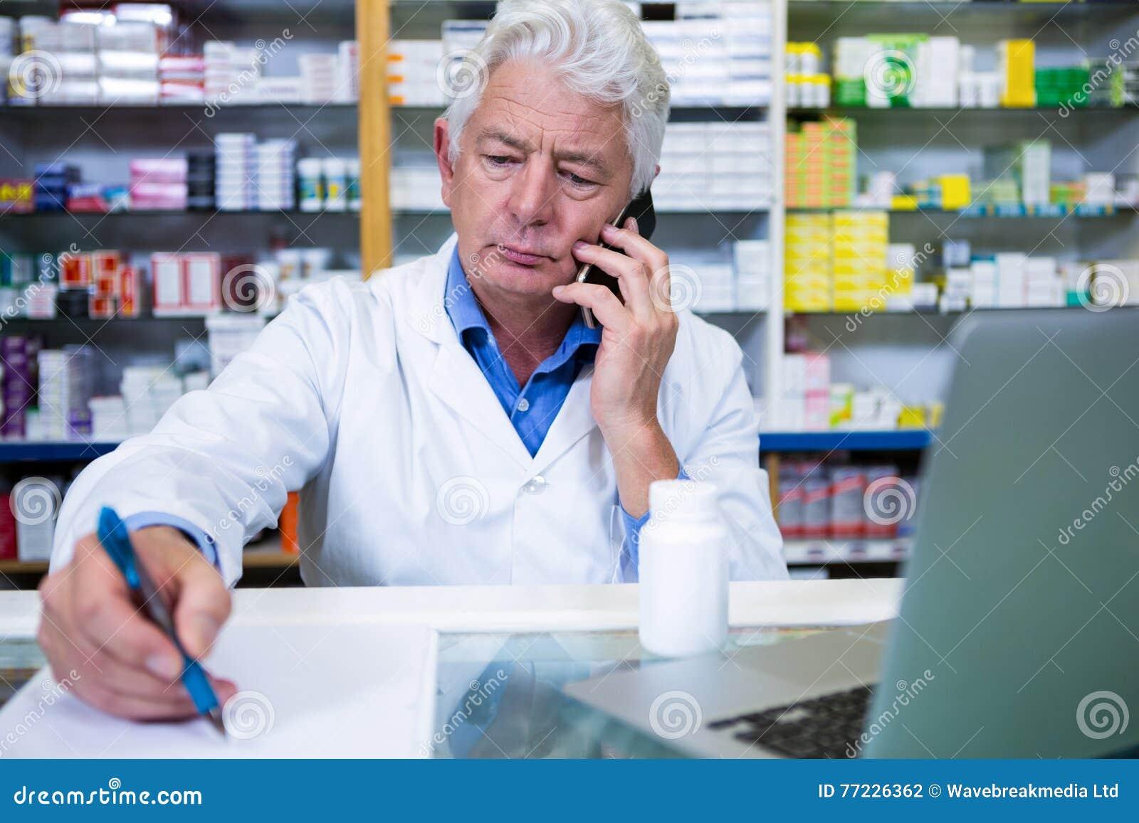 Apotheker die op mobiele telefoon spreken terwijl het schrijven van voorschriften