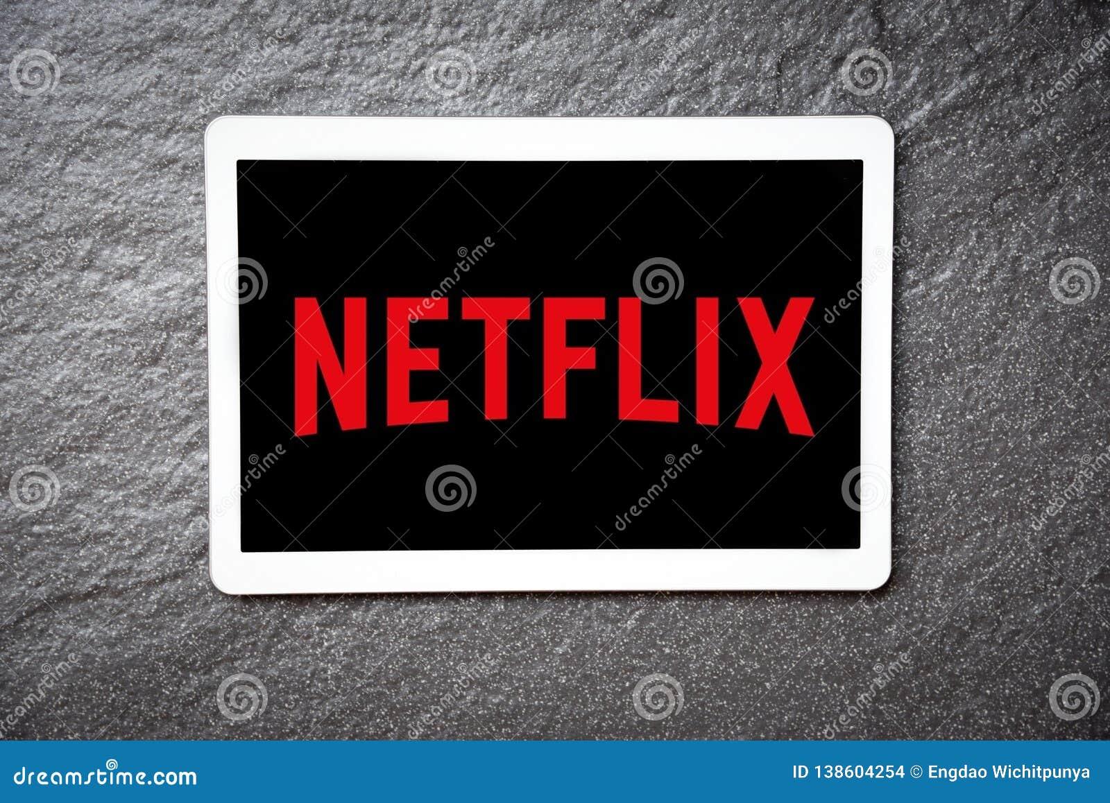 App de Netflix en el entretenimiento y películas de observación del servicio de la tableta con el logotipo de Netflix