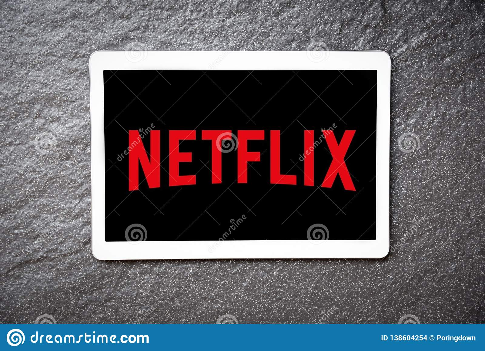 App di Netflix su spettacolo e sui film di sorveglianza di servizio della compressa con il logo di Netflix