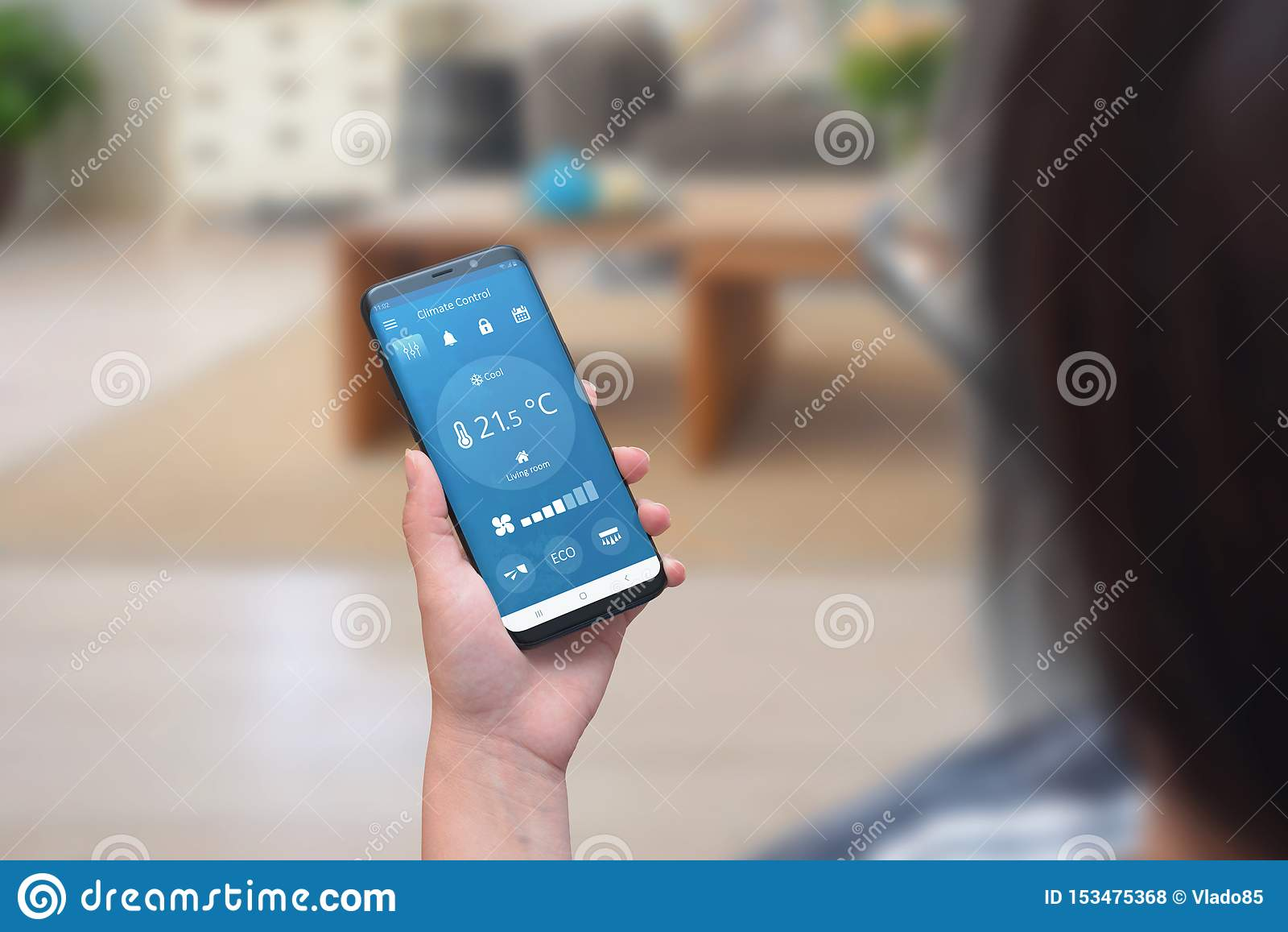 App do controle do clima do uso da mulher em um telefone na sala de visitas para ajustar a temperatura e a ventilação
