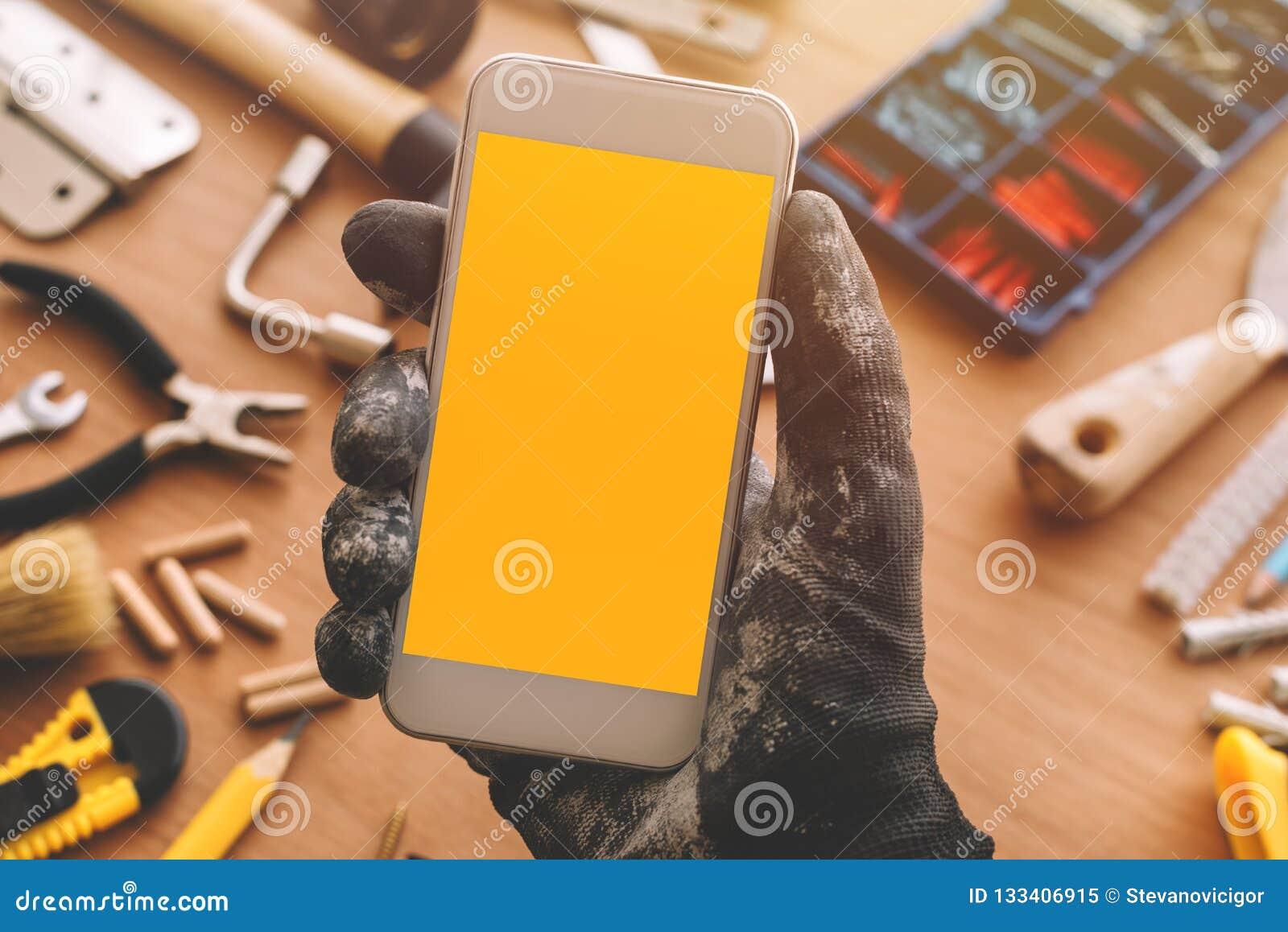 App elegante del teléfono del reparador, manitas que sostiene el teléfono móvil a disposición