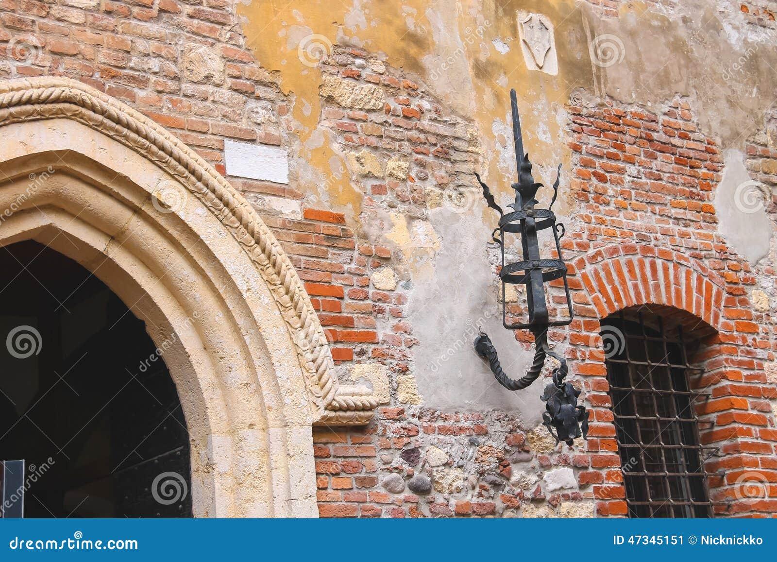 Apparecchio dilluminazione medievale sul vecchio muro di mattoni di