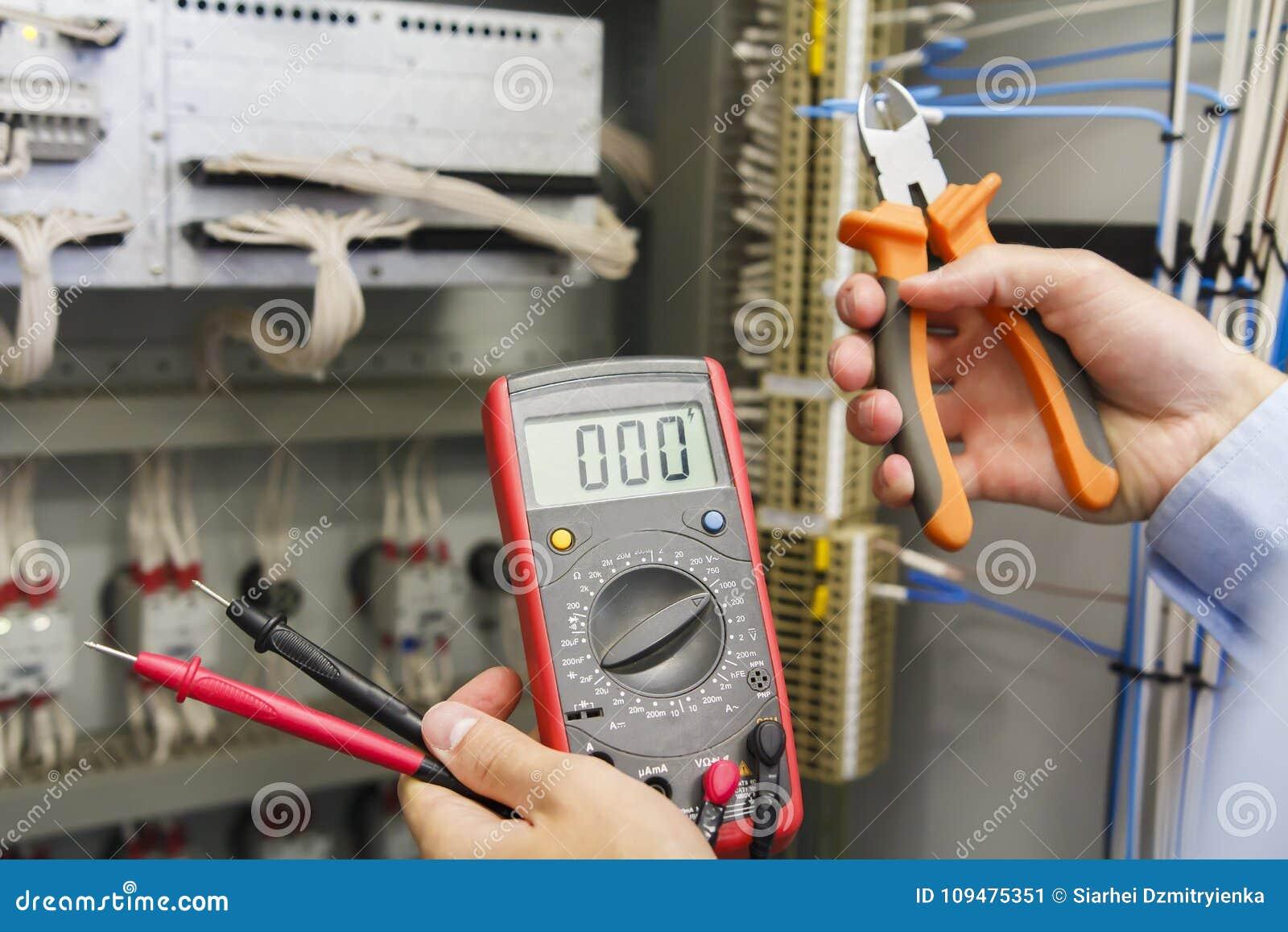 Appareil de contrôle et coupe-fil dans des mains d électricien contre le panneau de commande électrique de l équipement d automat