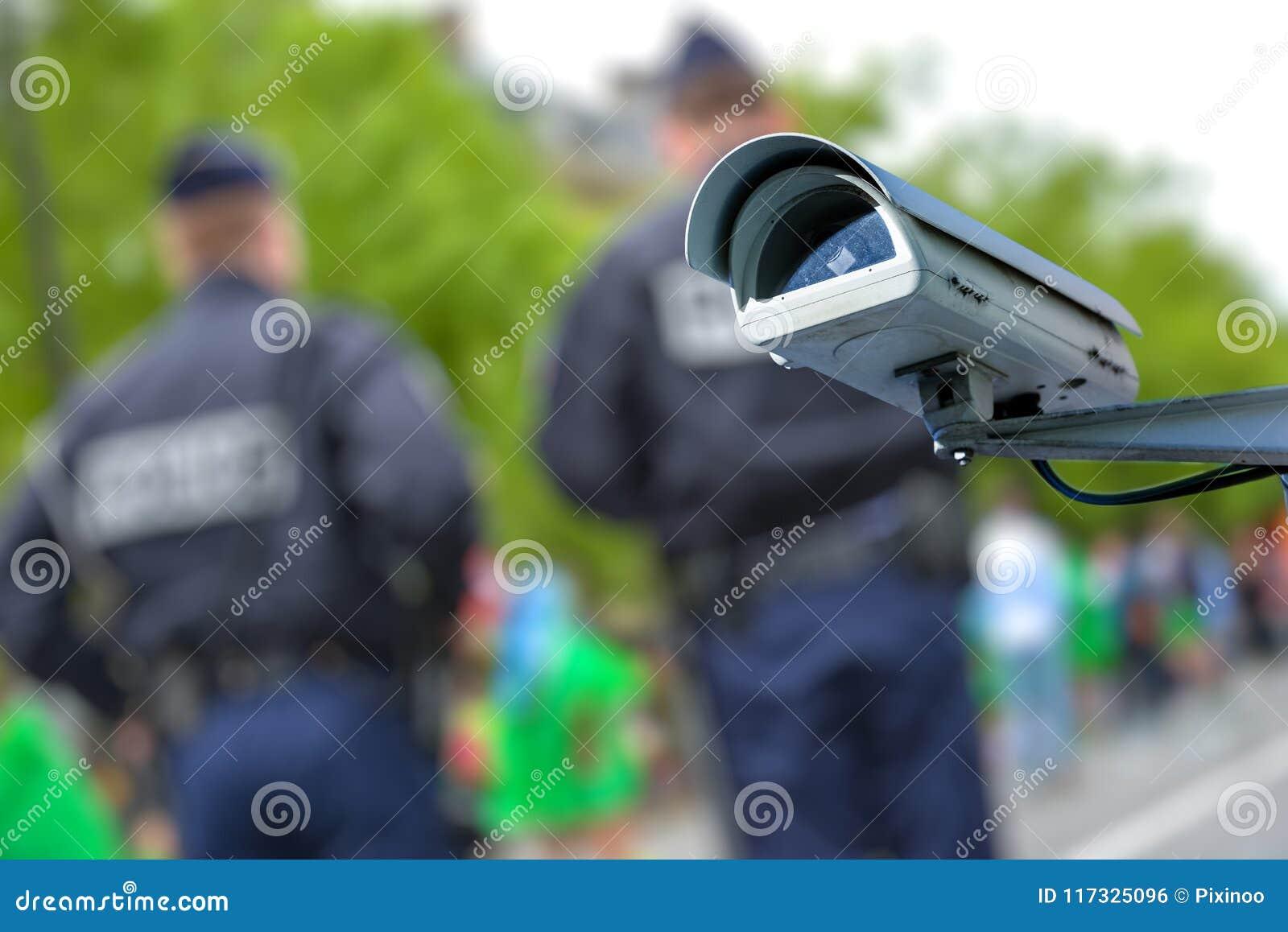 Appareil-photo de télévision en circuit fermé de sécurité ou système de surveillance avec des policiers sur le fond trouble