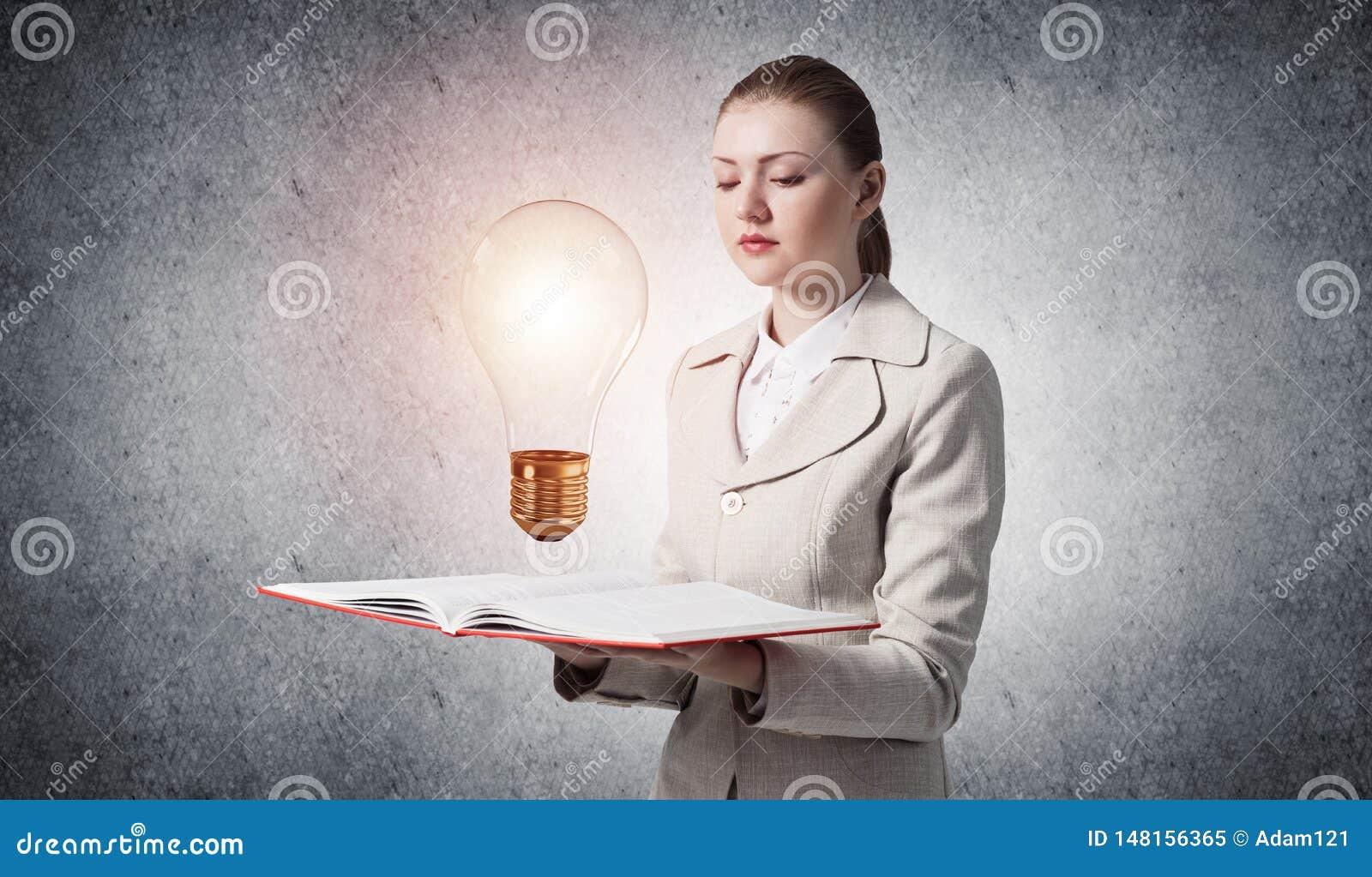 Apparence de femme brillant l ampoule sur le livre ouvert