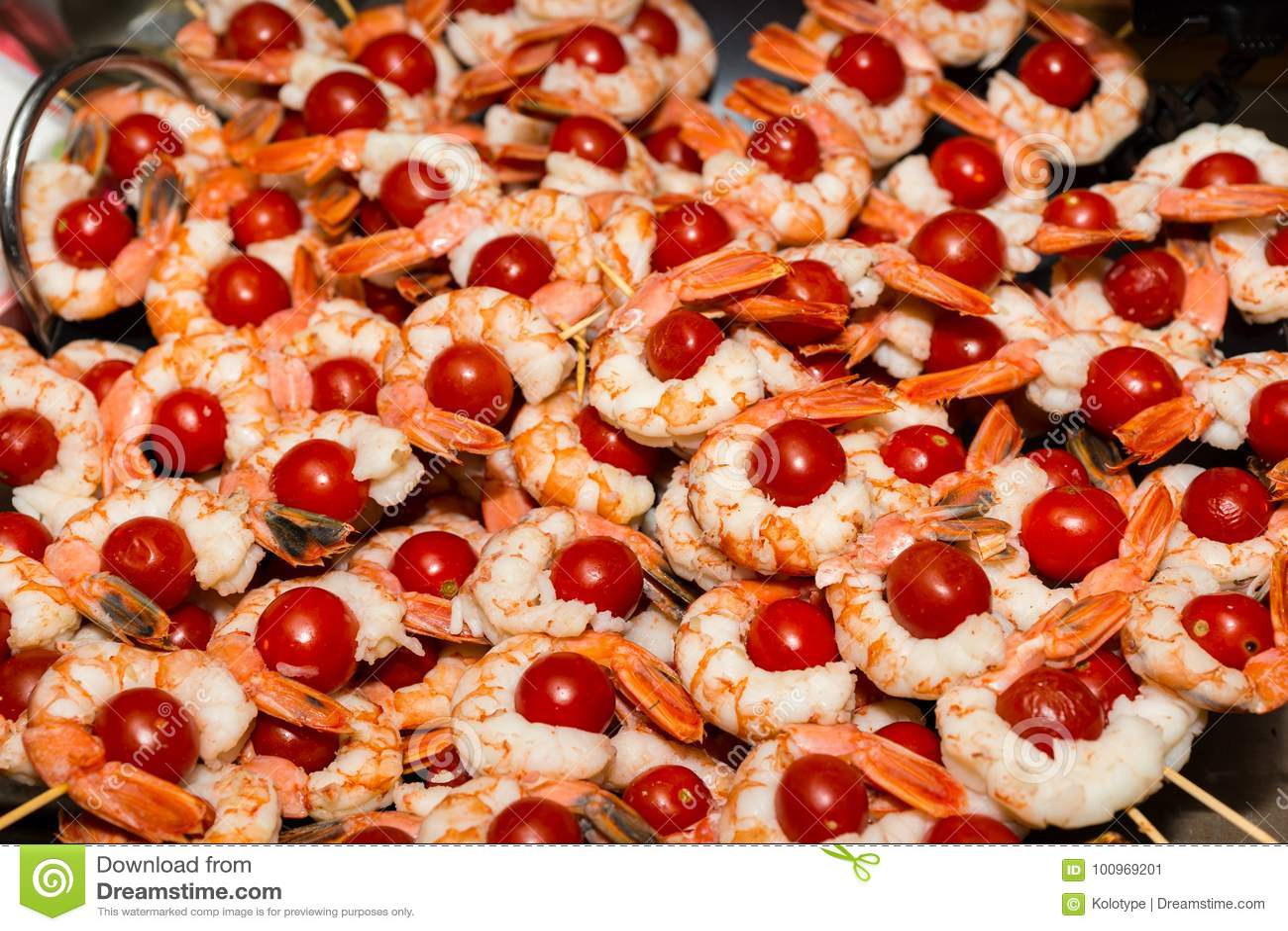 Appetitanregende gekochte Garnelen mit Tomaten auf Aufsteckspindeln an Lebensmittel festi