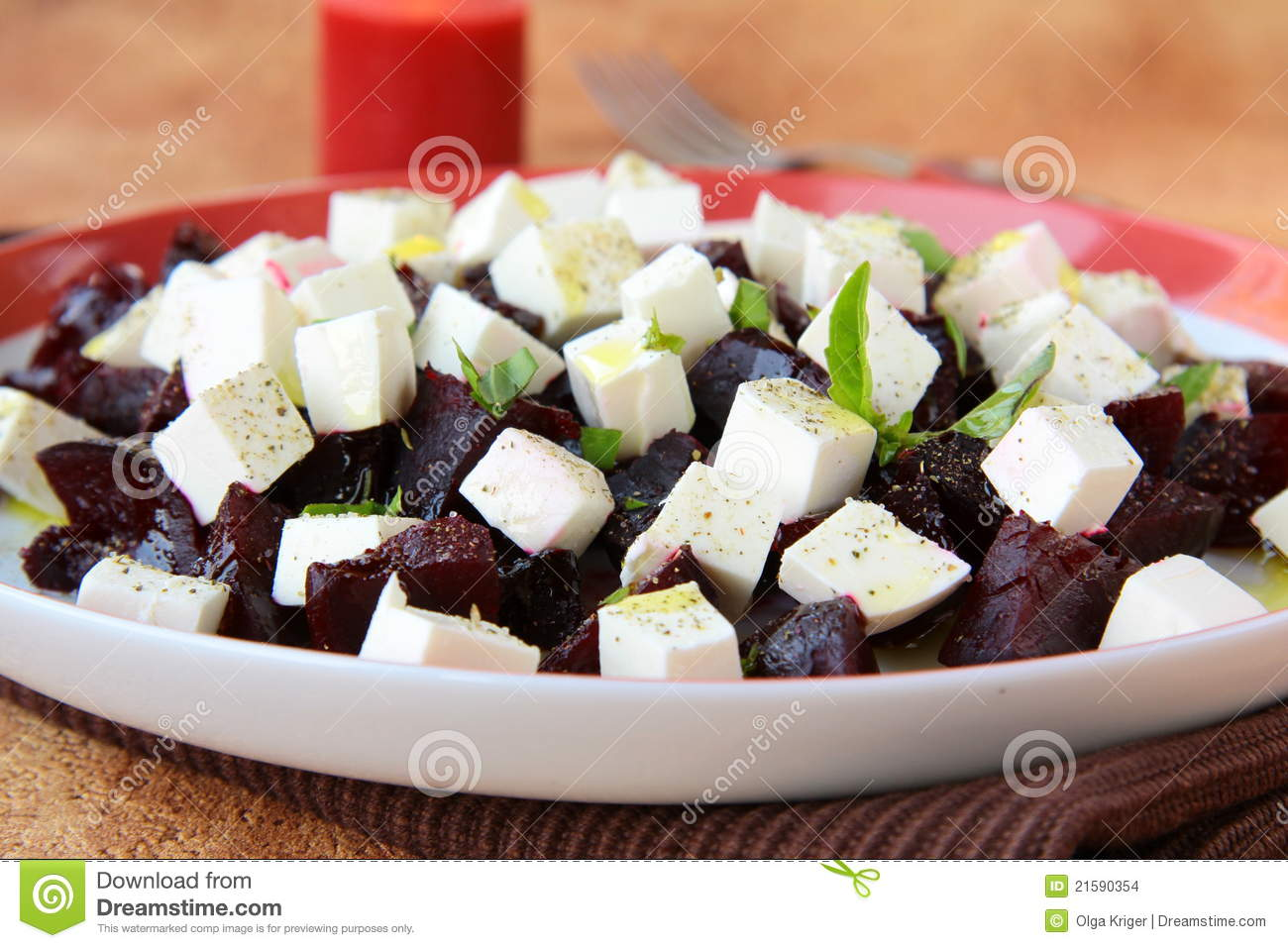 Appetizer salad of beets and goat cheese with basil and olive oil.