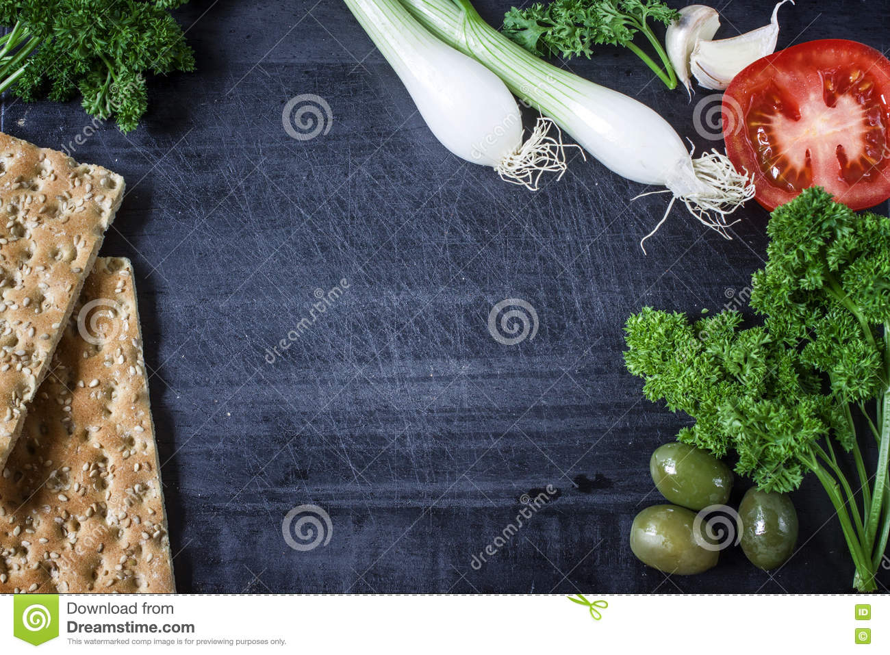 Appetizer set on wooden board. With olives,parsley,garlic. Top view. Dark background.