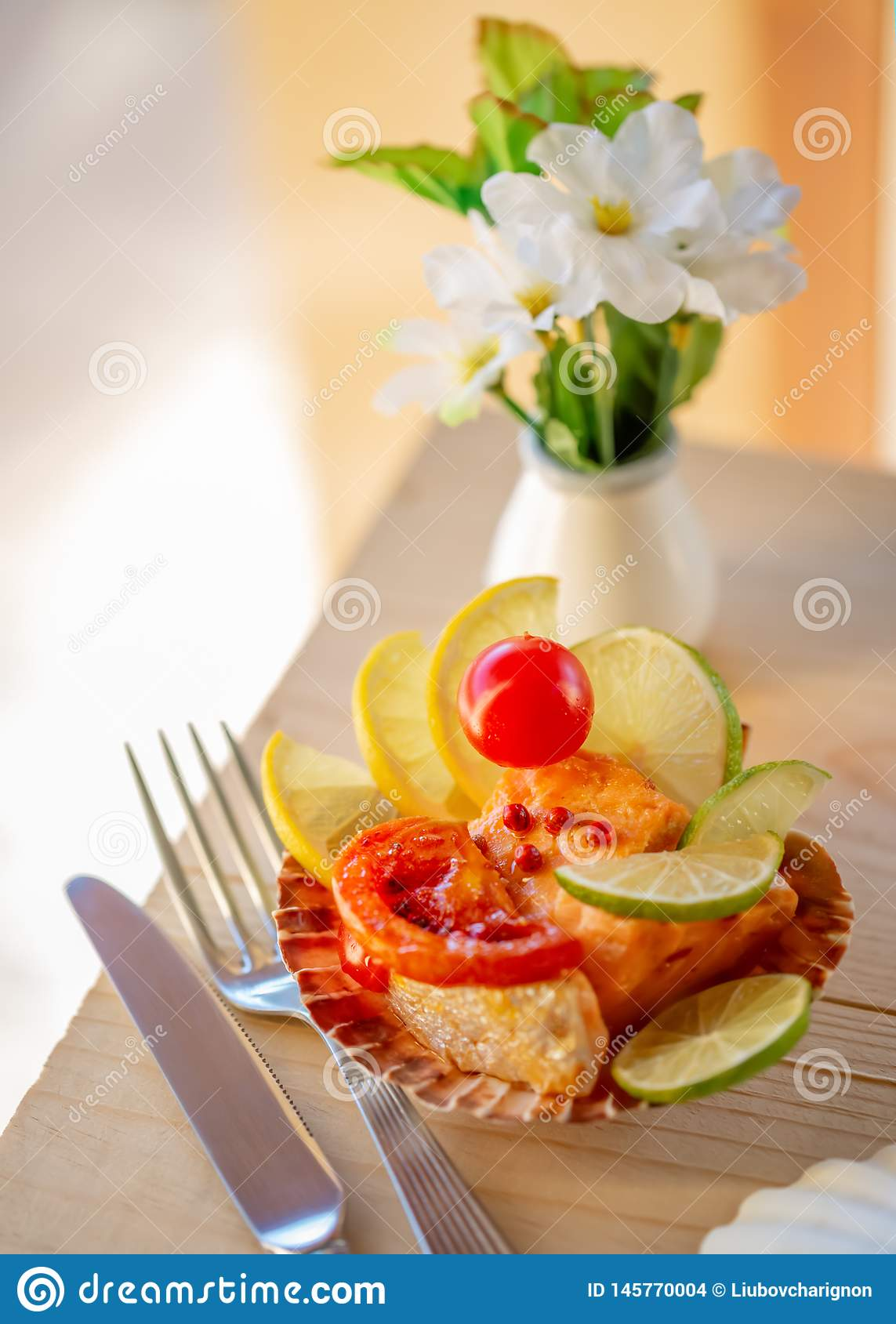 Appetizer on a wooden surface. Fish a salmon with slices of a lemon or lime and tomato on a plate.