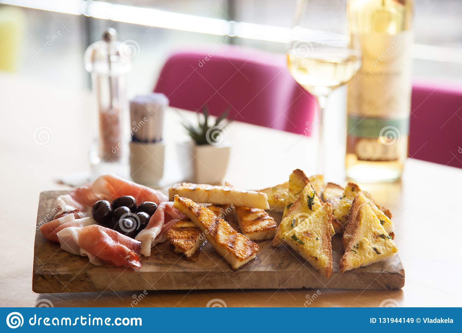 Appetizers table with italian antipasti snacks and wine in glass