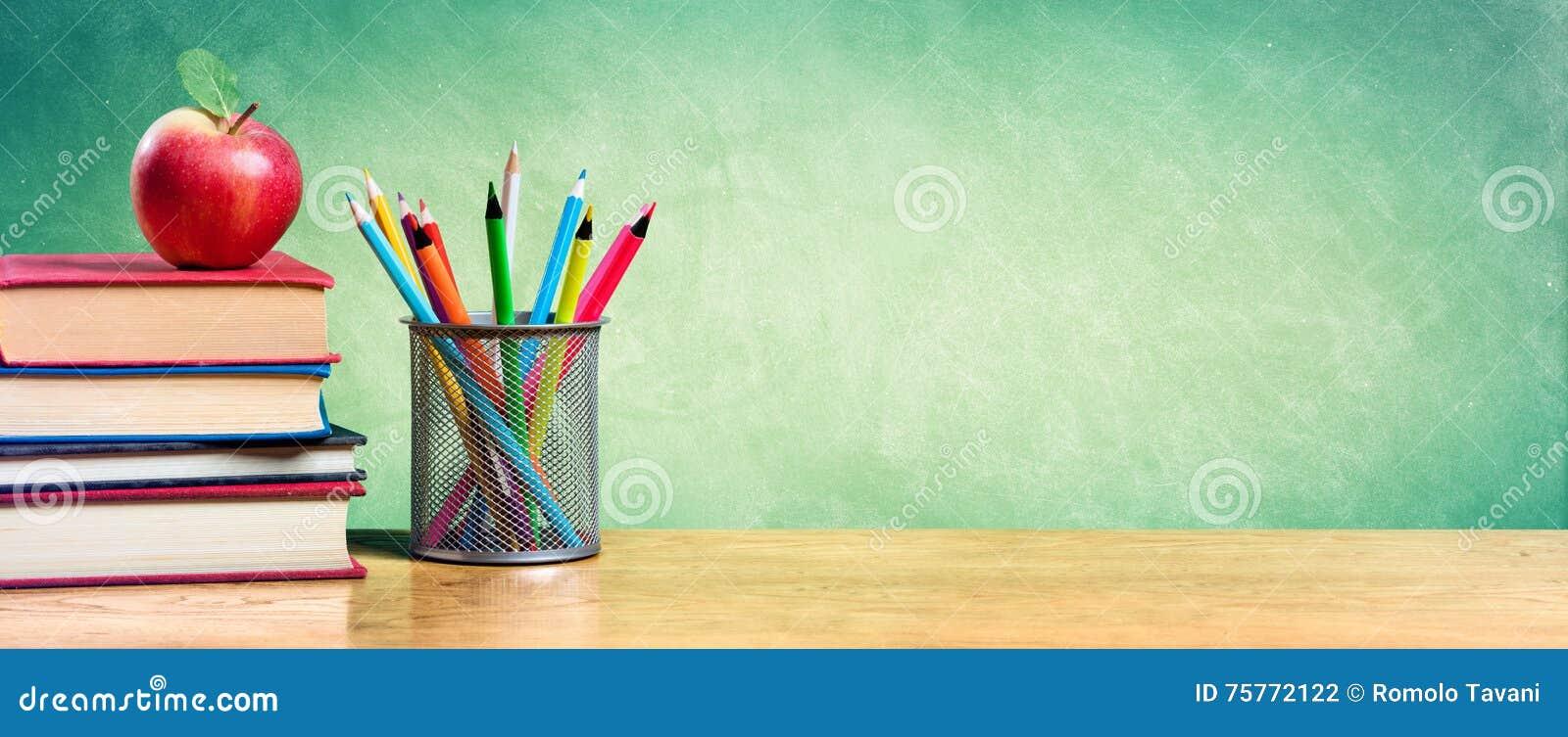 Apple auf Stapel Büchern mit Bleistiften und leerer Tafel