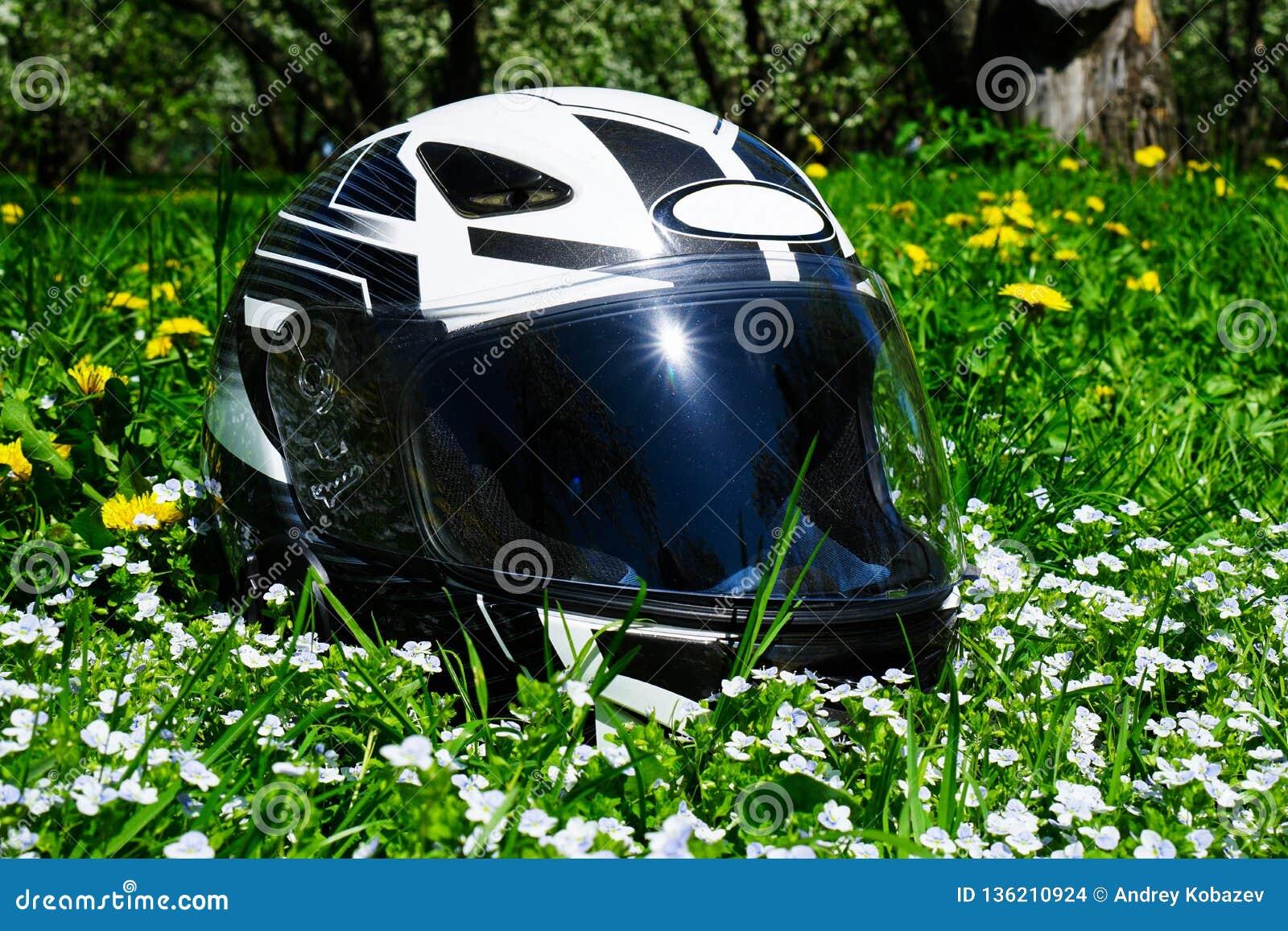 The helmet lies on a blooming meadow