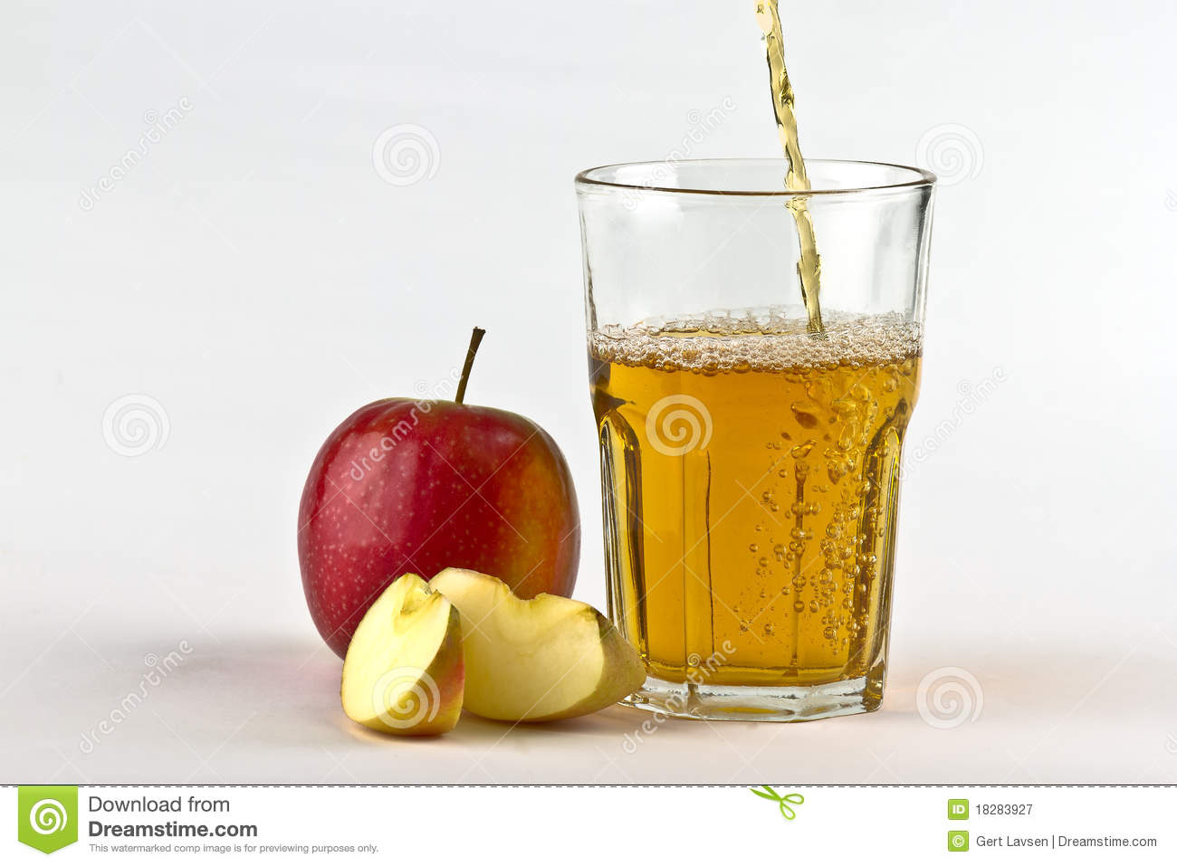 Apple cider pouring down into glass with apples at the side. On white ...