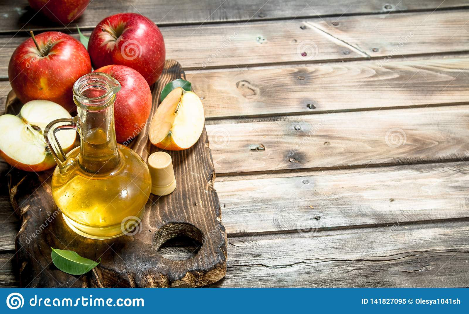 Apple cider vinegar with fresh red apples on a cutting Board
