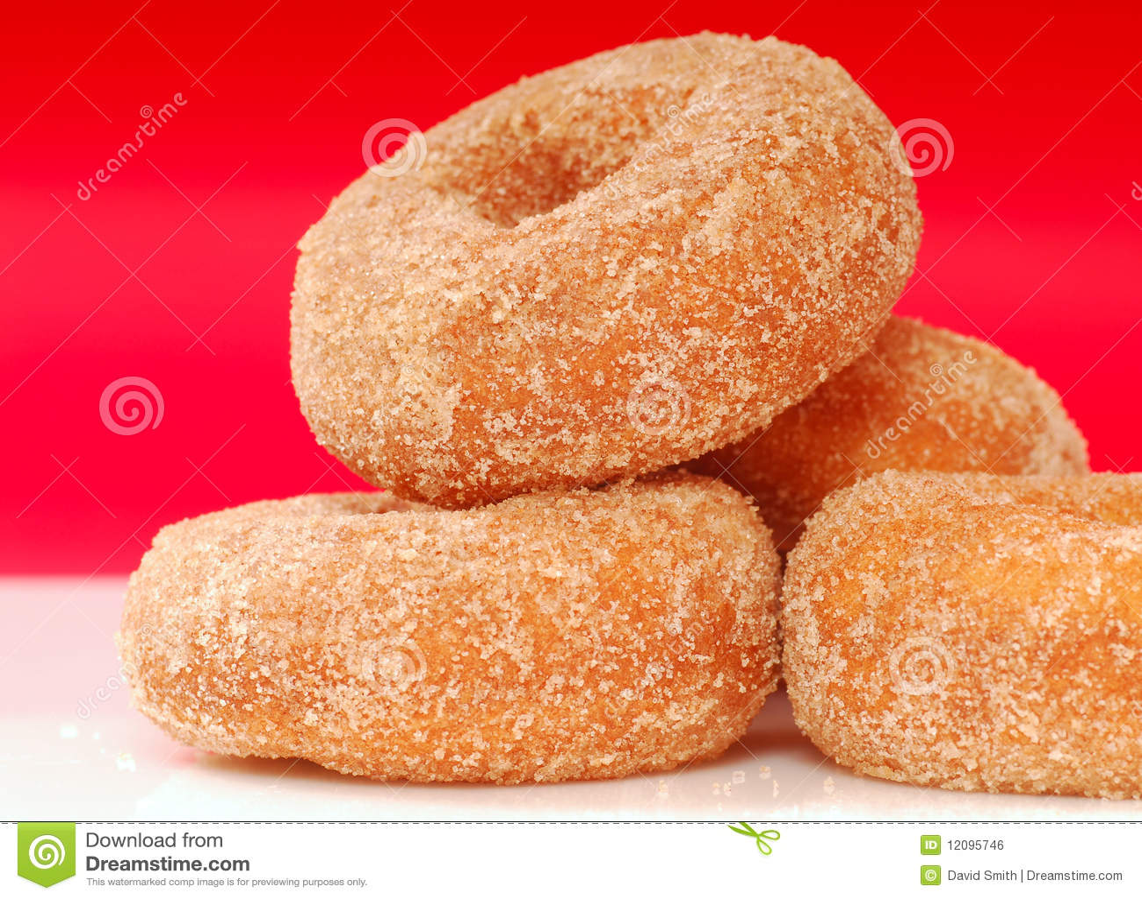 Freshly baked apple cinnamon donuts with cinnamon sugar.