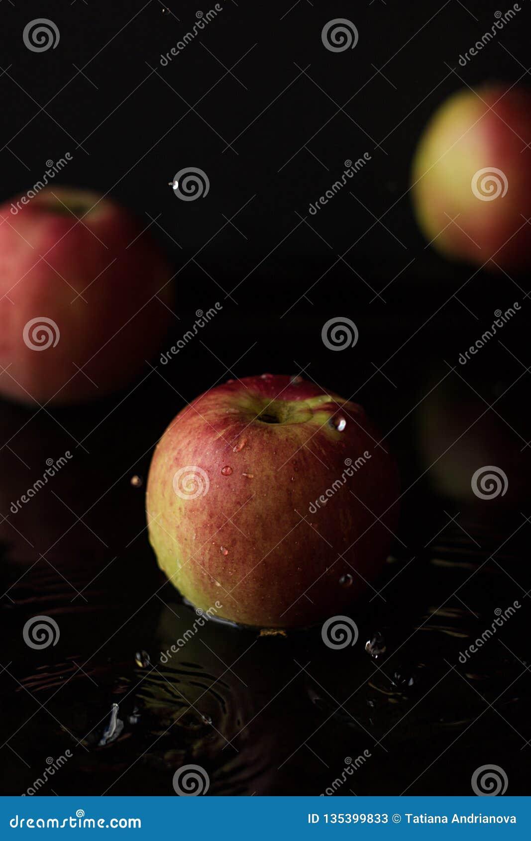 Apple com água deixa cair em um fundo preto Chave escura