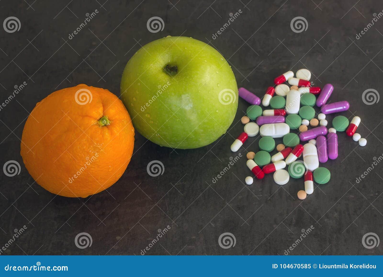 Apple et orange verts à côté des comprimés de vitamines et des supplemen