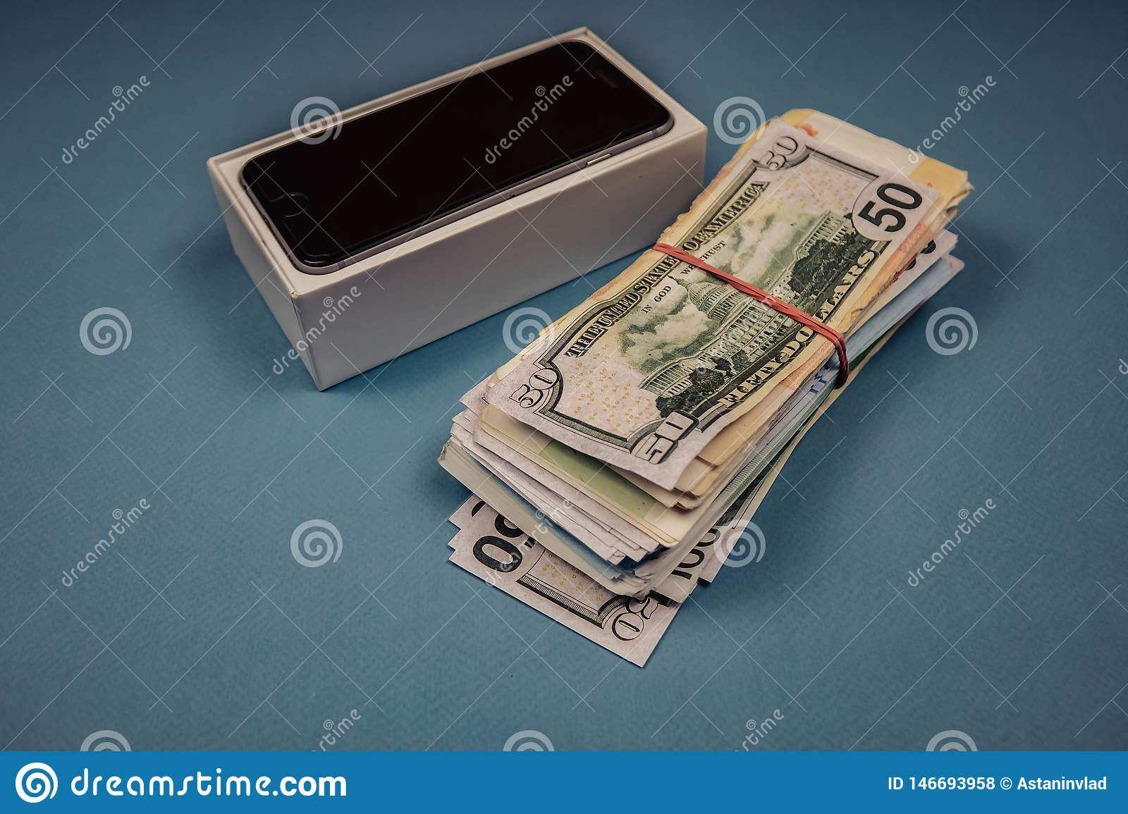 Apple iPhone devices and dollars on a blue monophonic background. Voronezh, Russia - May 3, 2019