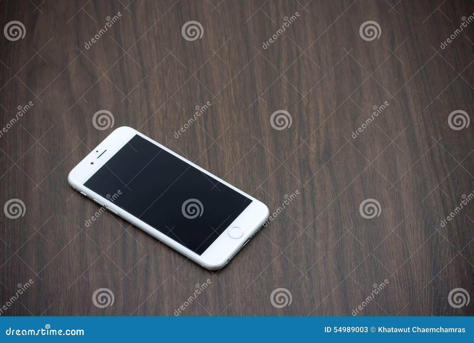 Apple Iphone 6 i vit färg med den tomma skärmen som lägger på trä
