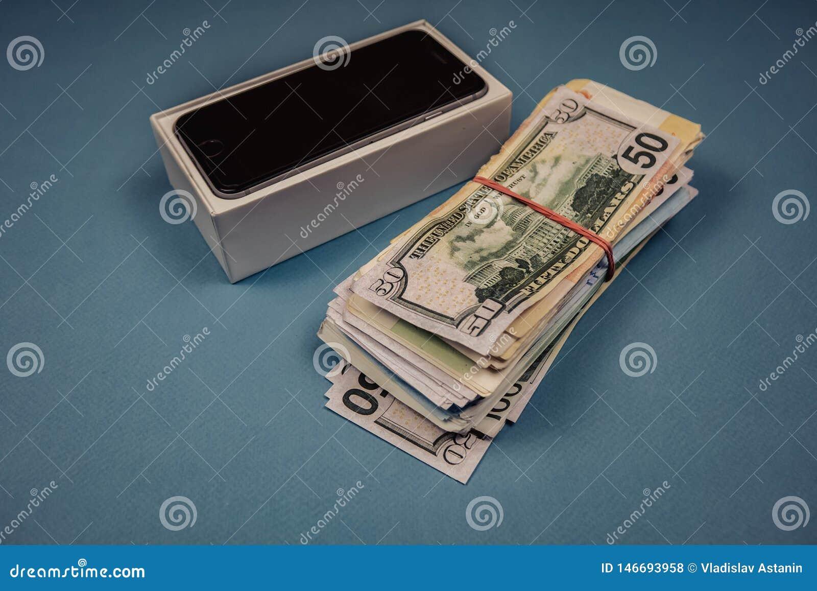 Apple iPhoneapparater och dollar p? en bl? monophonic bakgrund Voronezh Ryssland - Maj 3, 2019