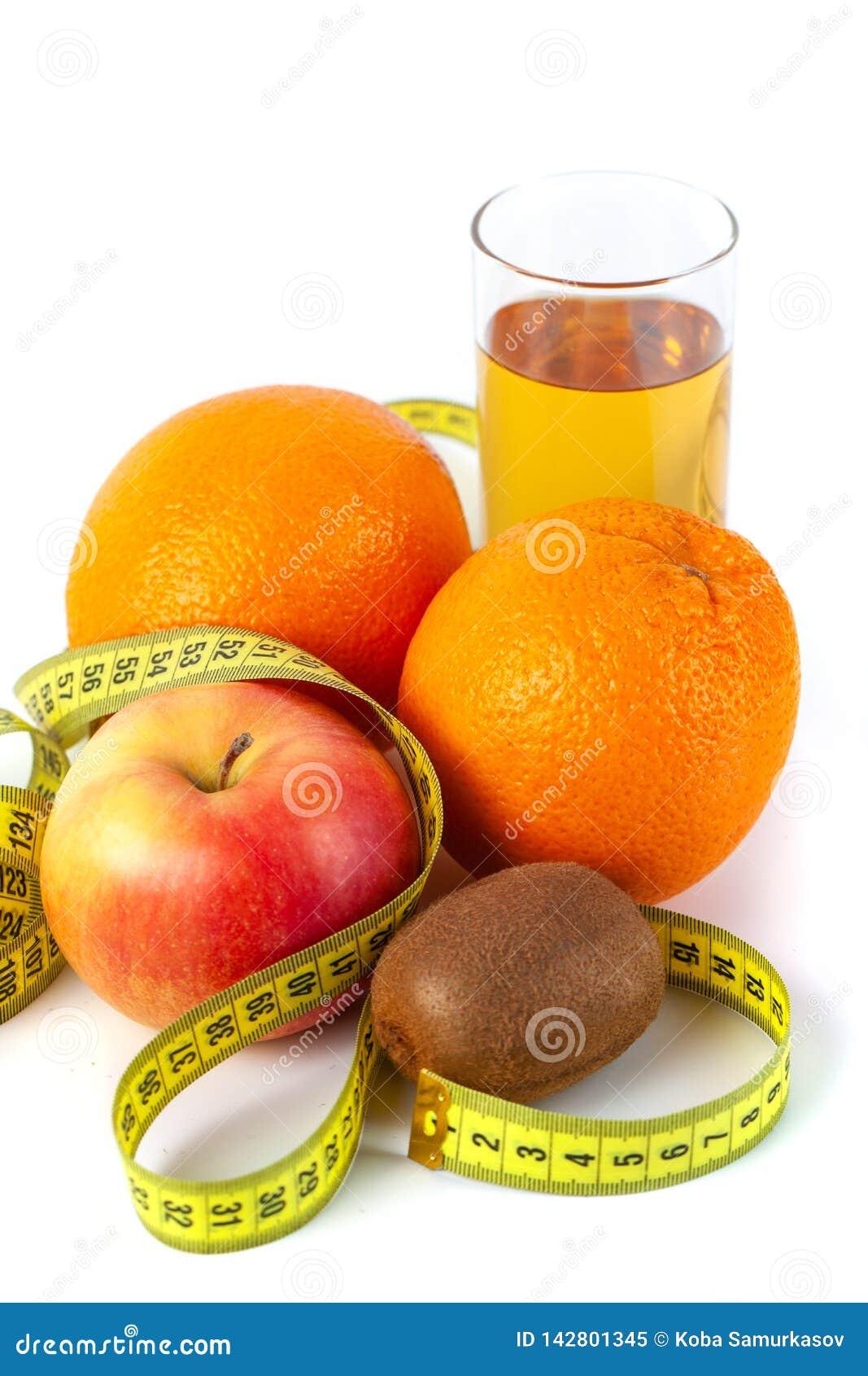 Apple, laranja, quivi e suco de maçã com fita métrica no fundo branco