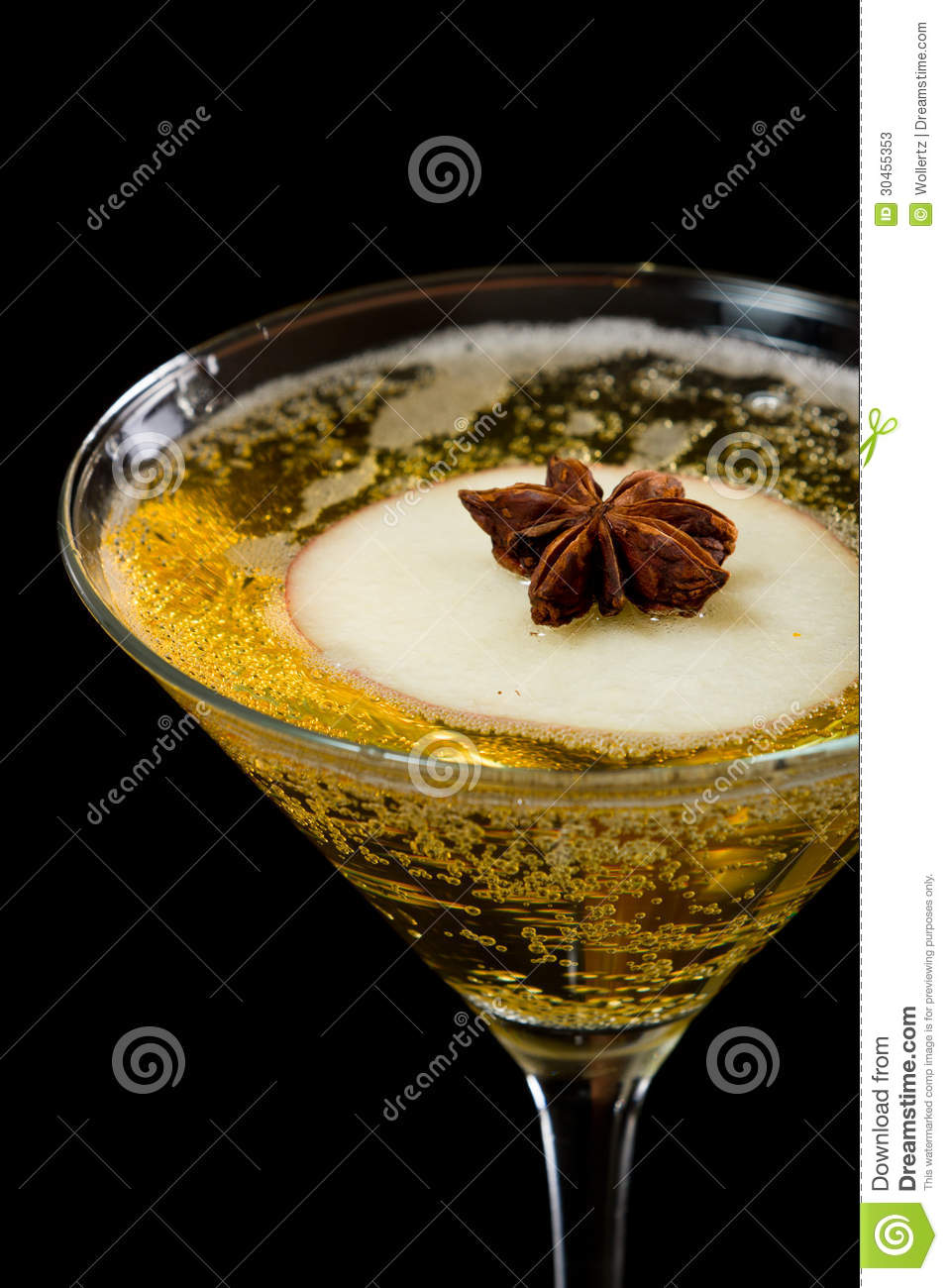 Sparkling apple martini on a dark bar with an anise star floating on ...