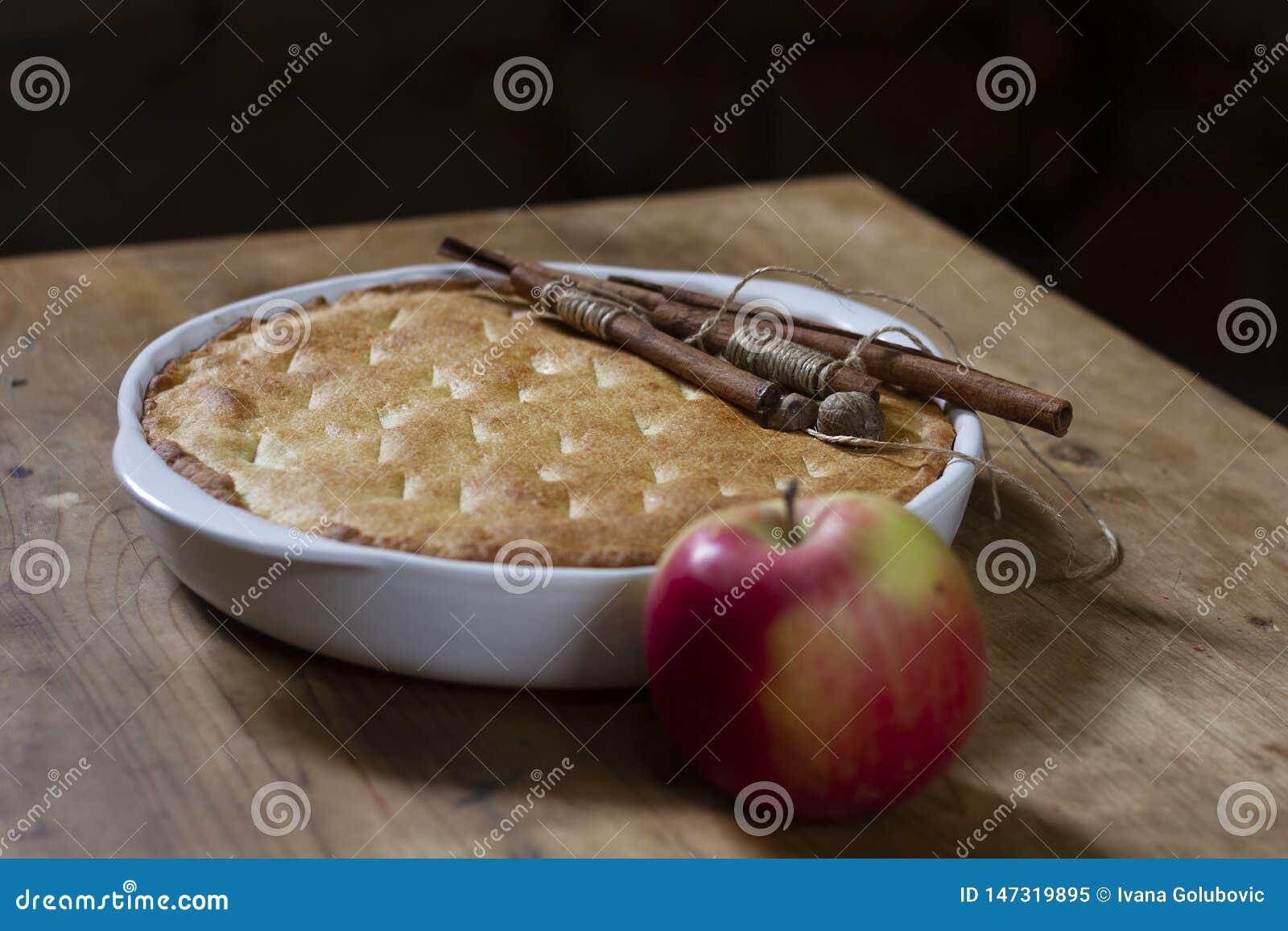 Apple pie in a white ceramic baking dish with cinnamon sticks