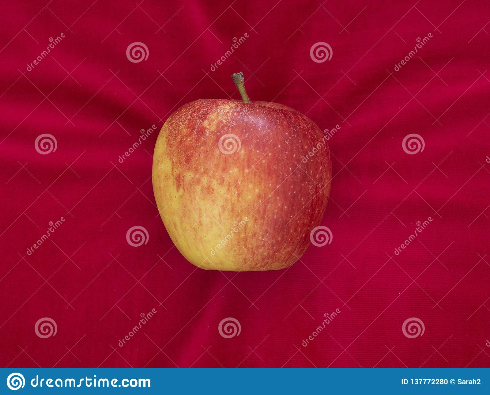 Apple on red velvet cushion, temptation or luxury, with copyspace.