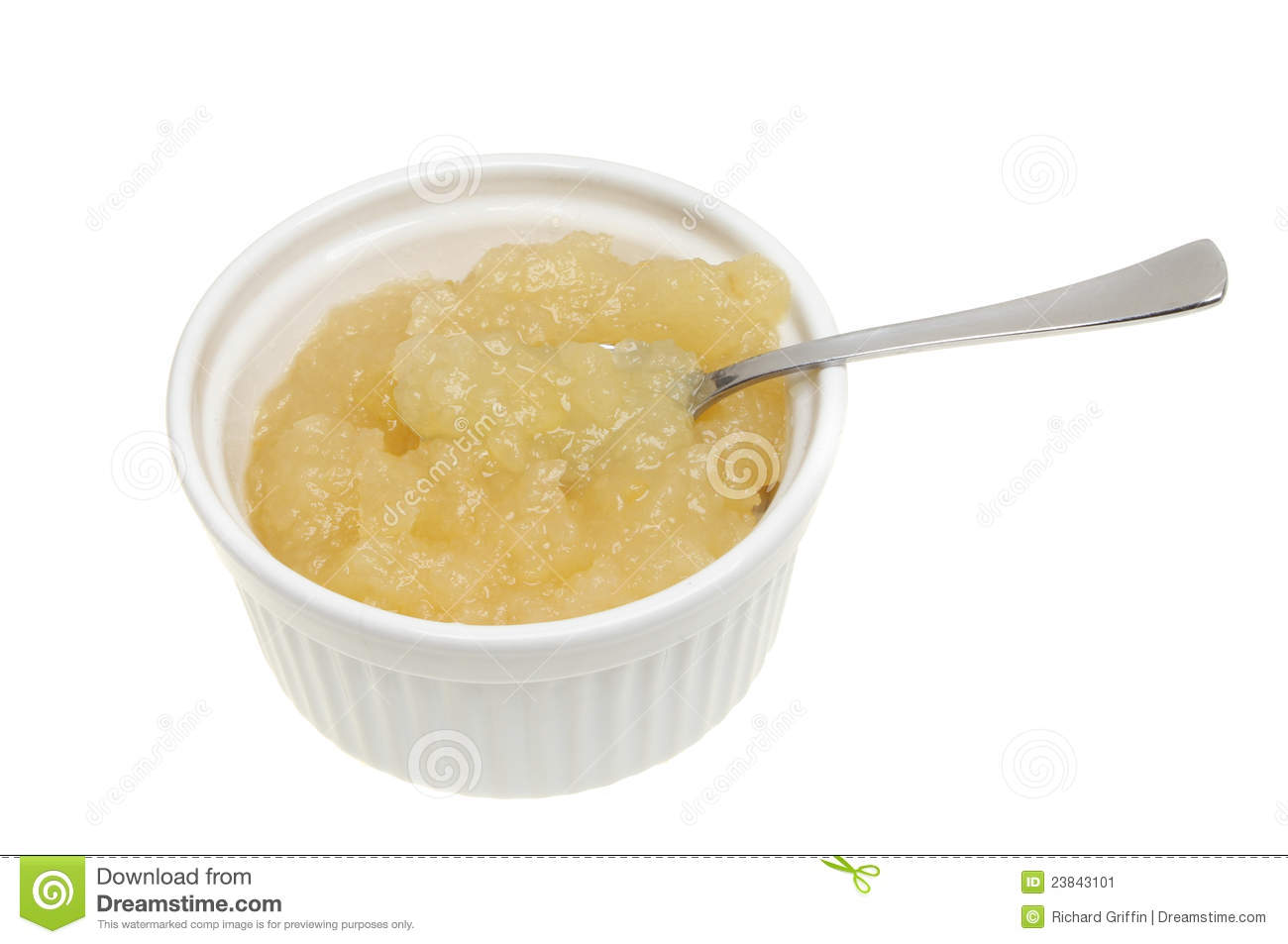 Apple sauce with a spoon in a ramekin isolated against white.