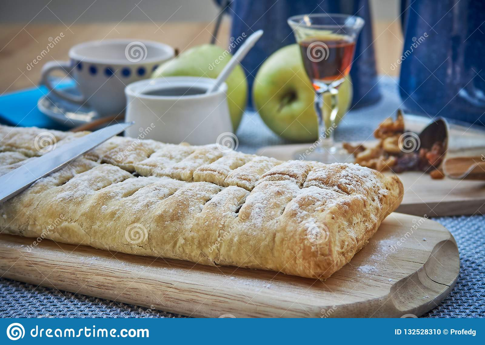 Apple strudel with nuts, raisins, cinnamon and powdered sugar. Homemade apple strudel with fresh apples. Country style apple