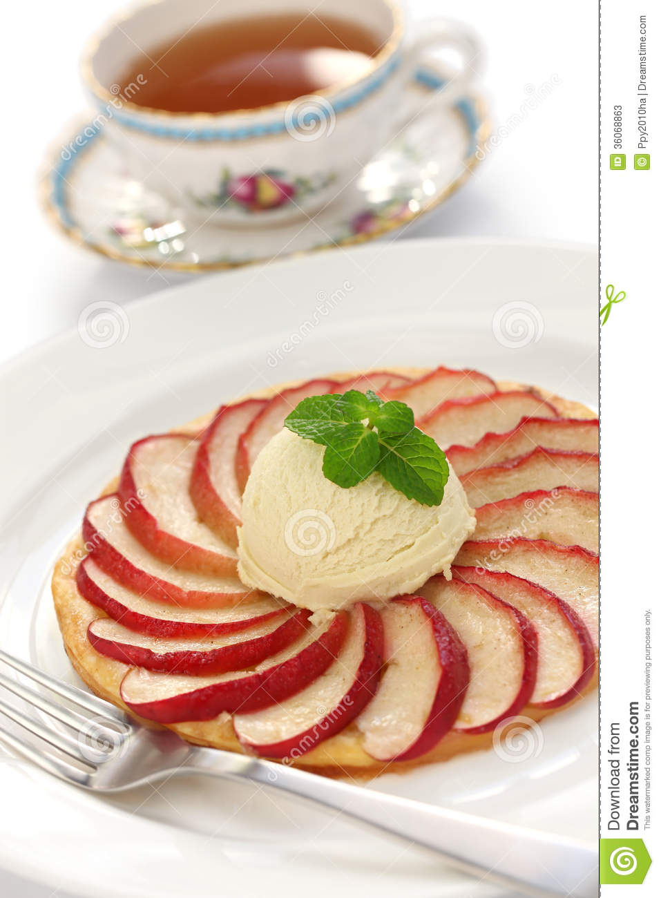 Apple tart, flat apple pie with ice cream and a cup of tea.
