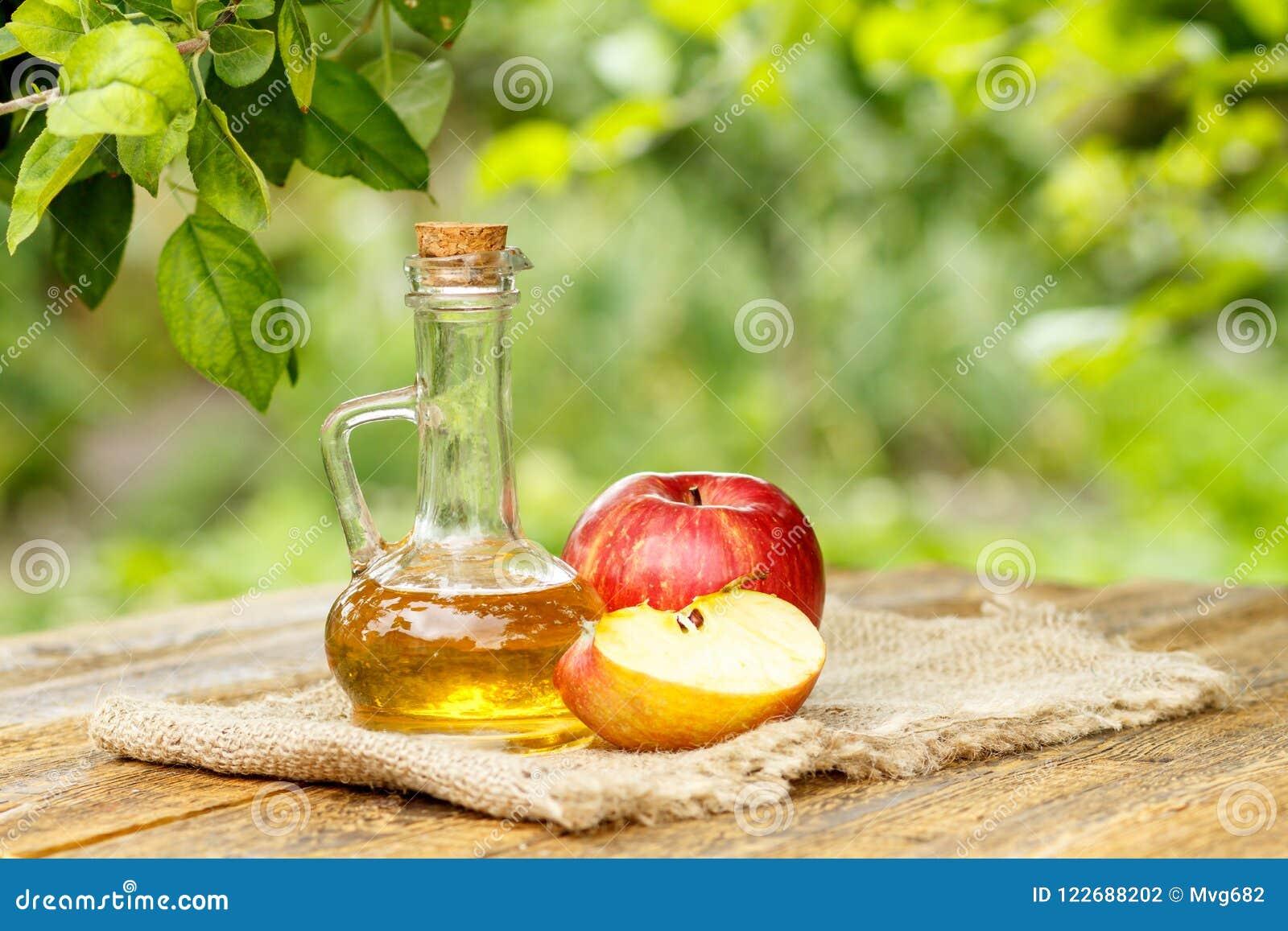 Apple vinäger i glasflaska och nya röda äpplen på träboa