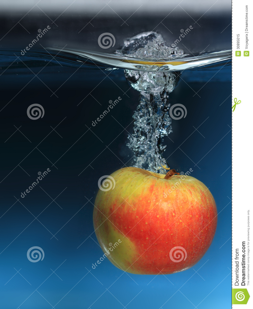 Apple In The Water Splash Over Blue Background Royalty