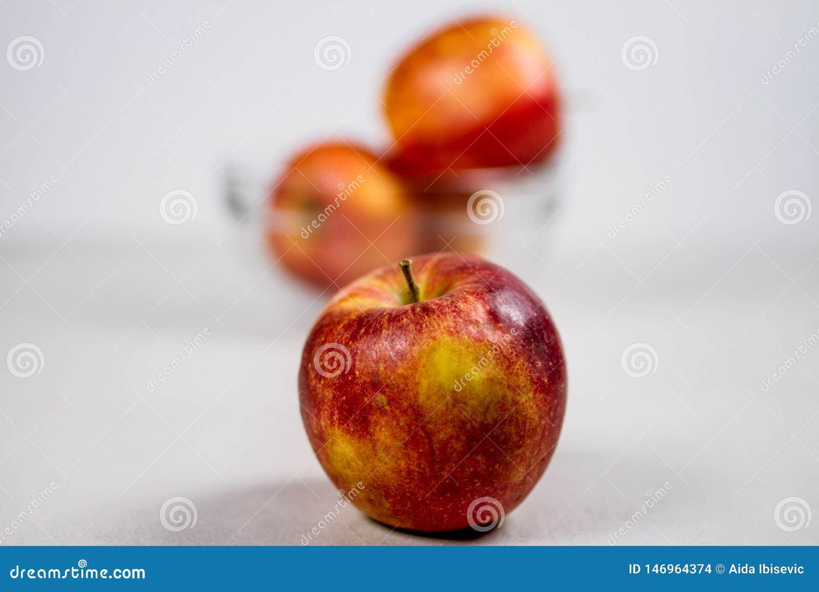 Apple y bol de vidrio jugosos rojos con las manzanas aisladas en el fondo blanco