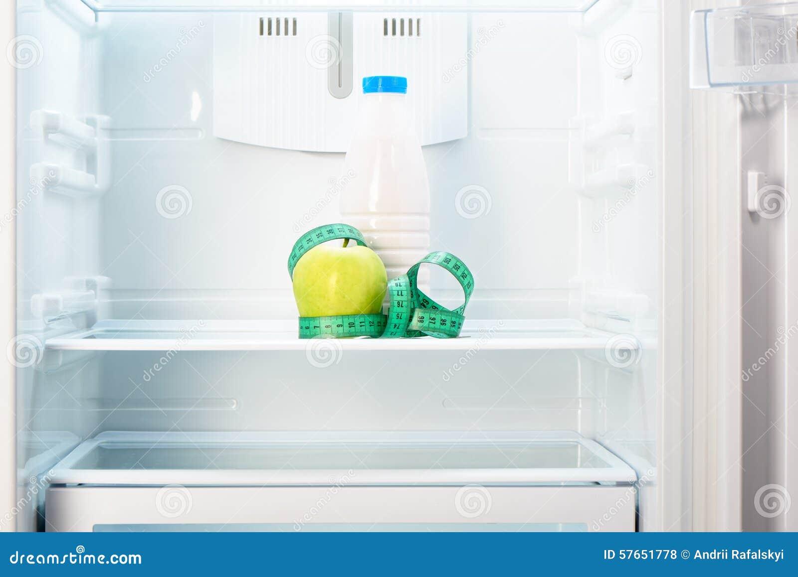 Apple z pomiarową taśmą i butelką na półce chłodziarka