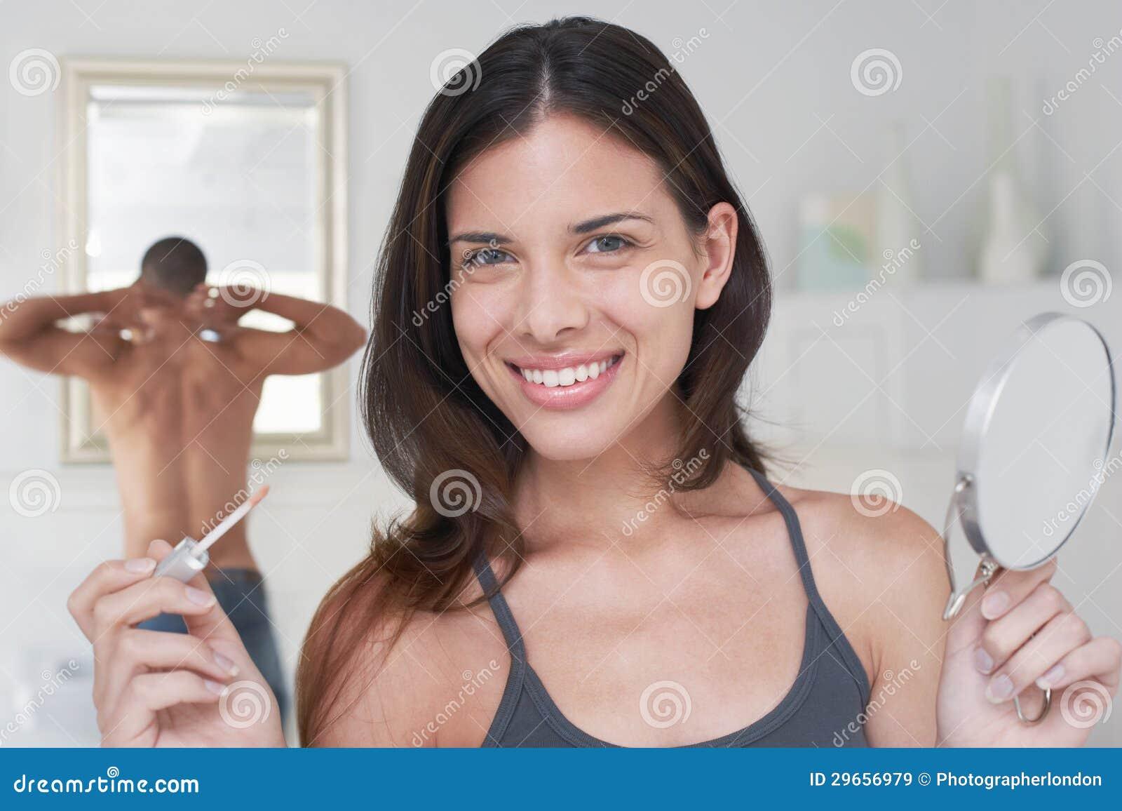 Applicatore e specchio felici della tenuta della donna