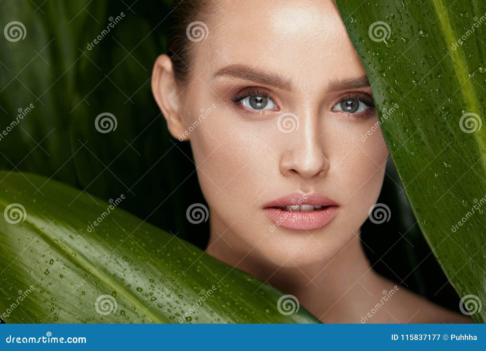 Applicera genomskinlig fernissa för omsorgshud Härlig kvinna med naturlig makeup