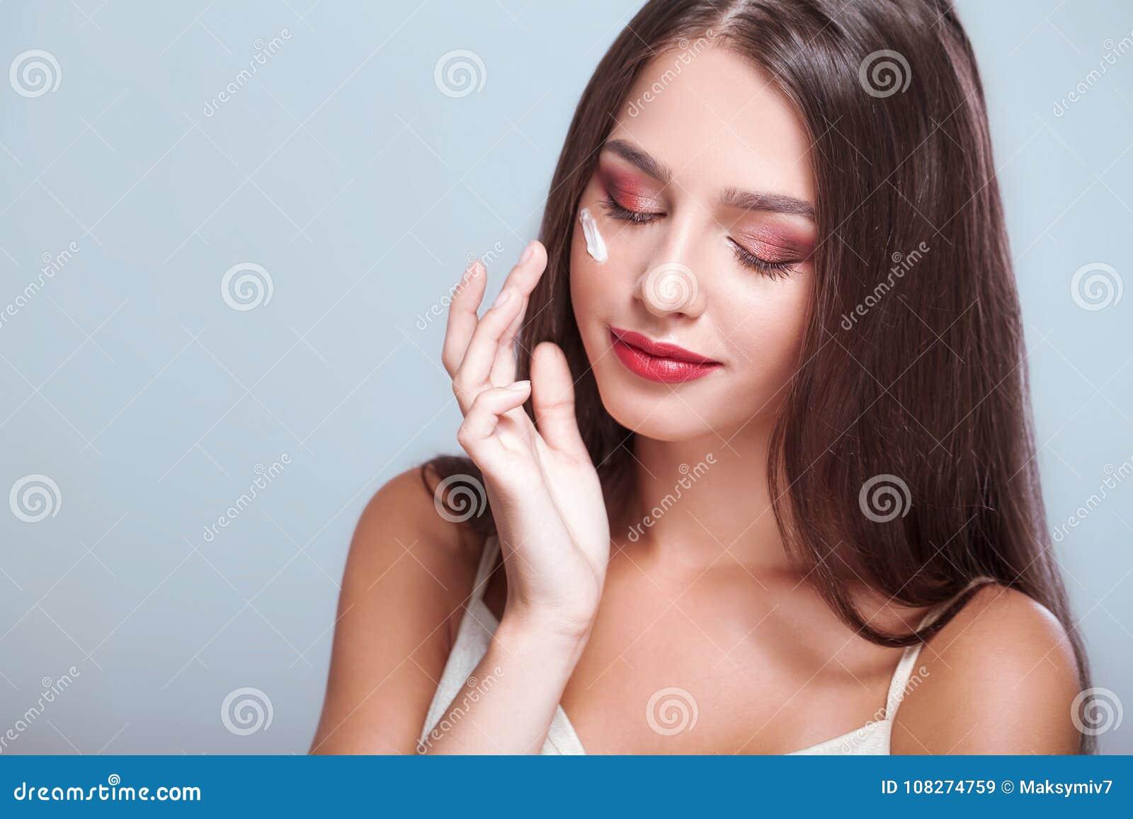 Applicera genomskinlig fernissa för omsorgshud Skönhetframsida av kvinnan med skönhetsmedelkräm på framsida _