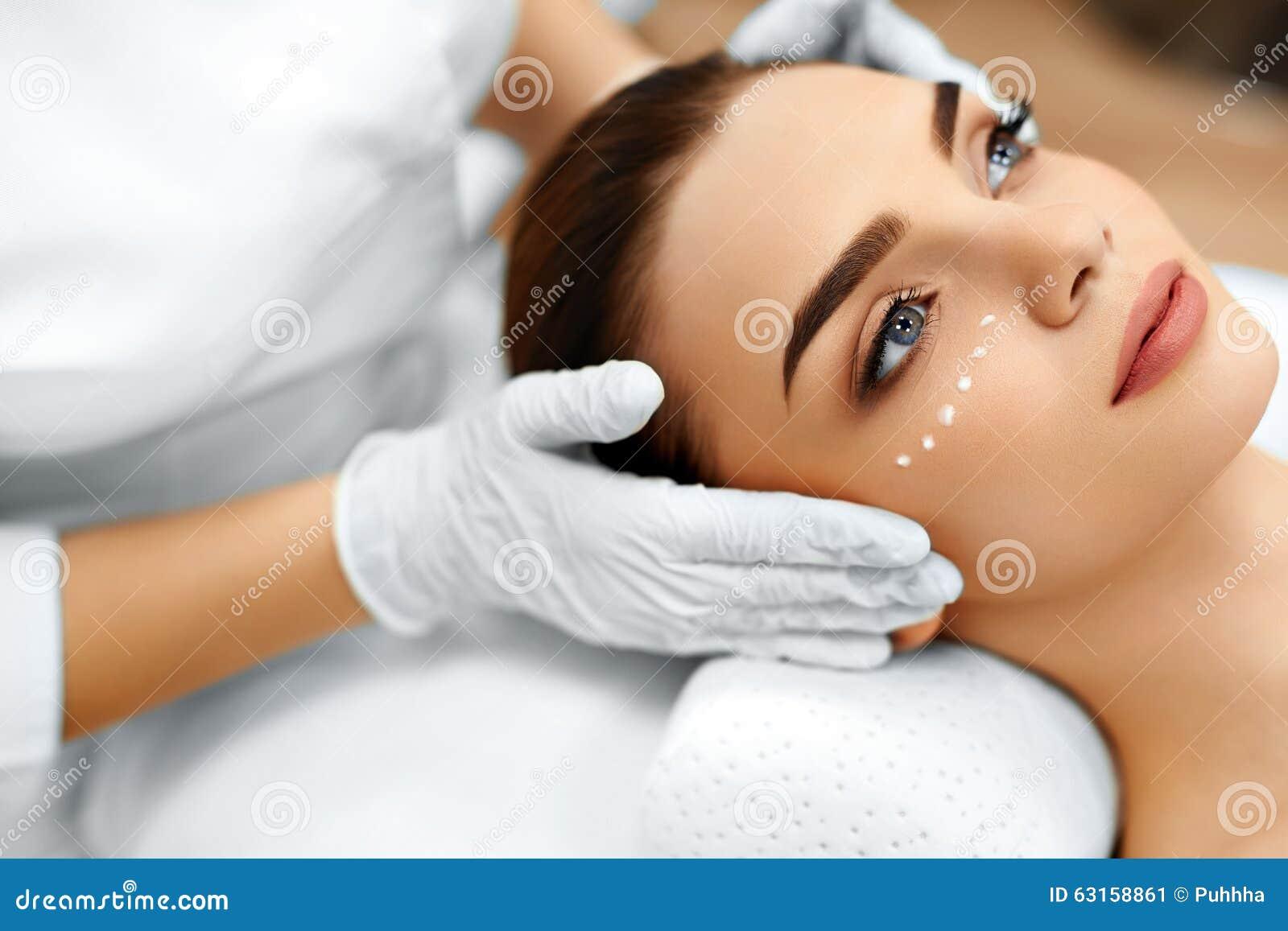 Applicera genomskinlig fernissa för omsorgshud Skönhetsmedelkräm på kvinnas framsida Le ung kvinna med tumen upp