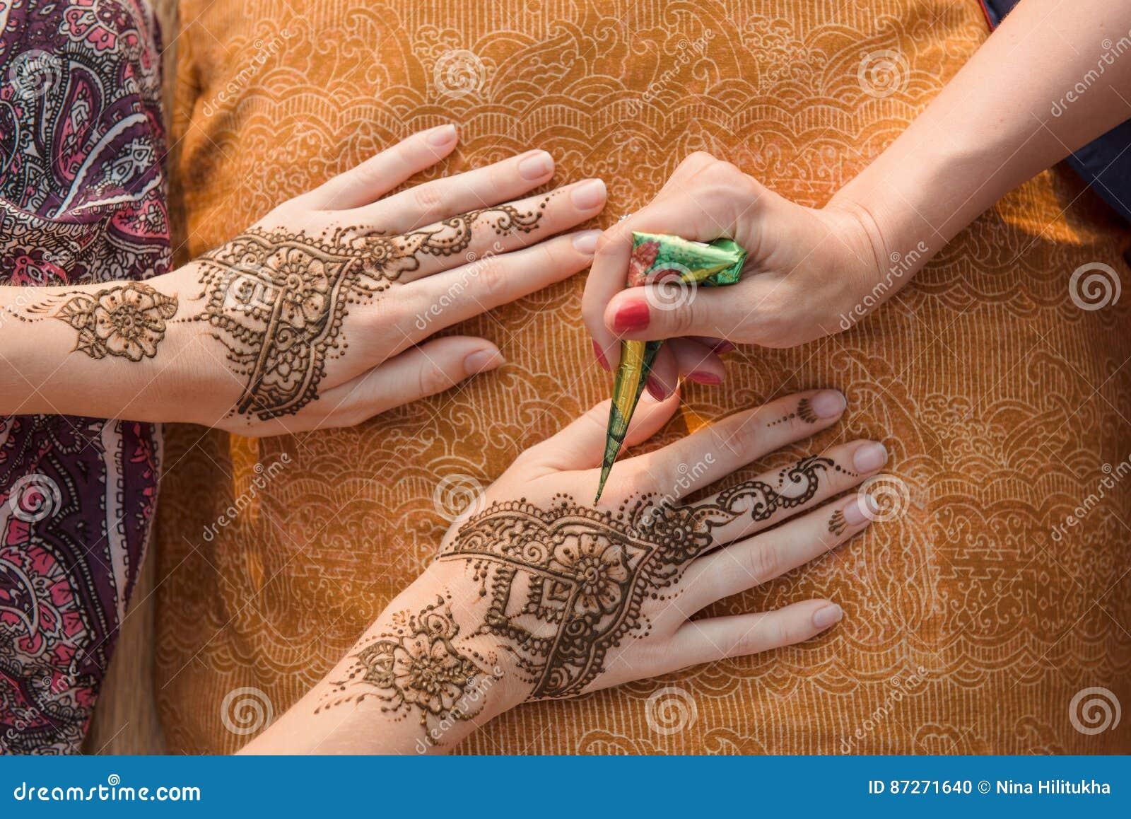 Applying Henna Tattoo On Women Hands Stock Photo , Image of