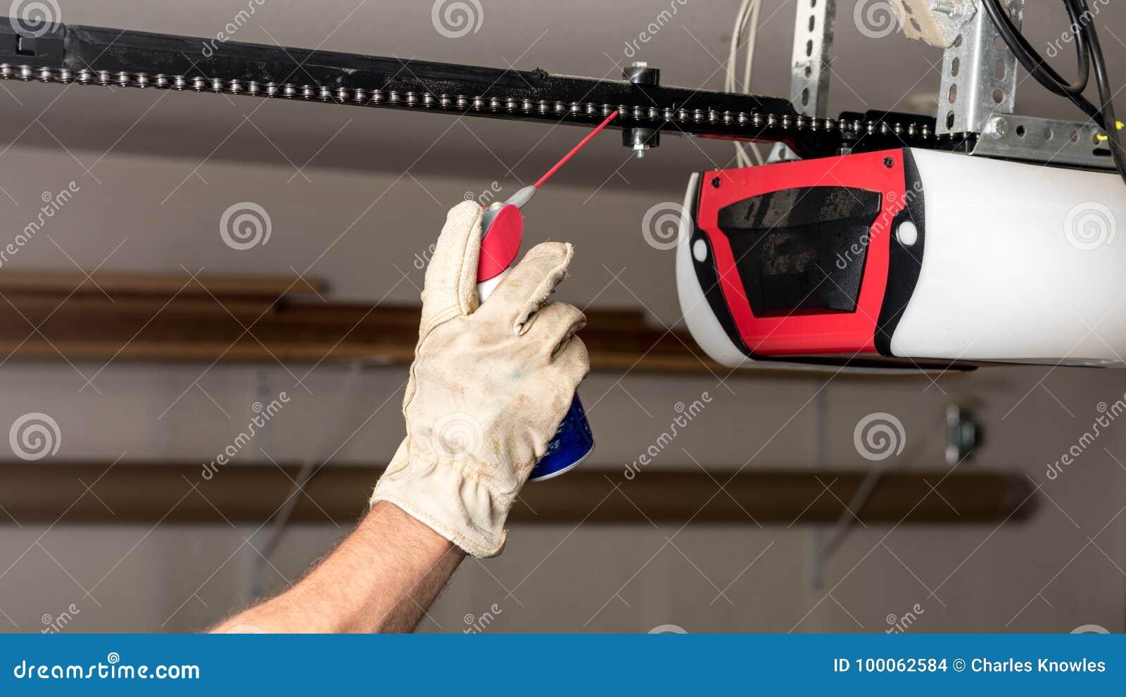 Applying Oil To A Chain Of A Garage Door Opener Stock
