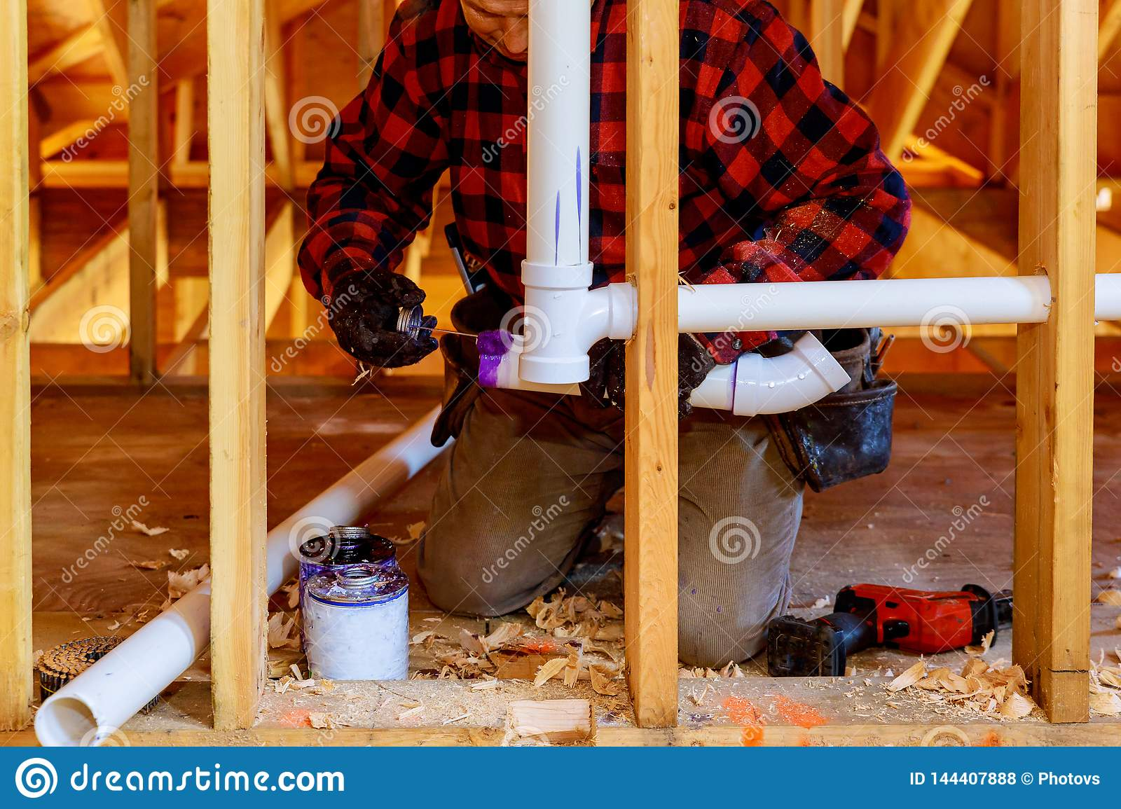 Applying plumber pipe drain and vent plumbing system at new home construction