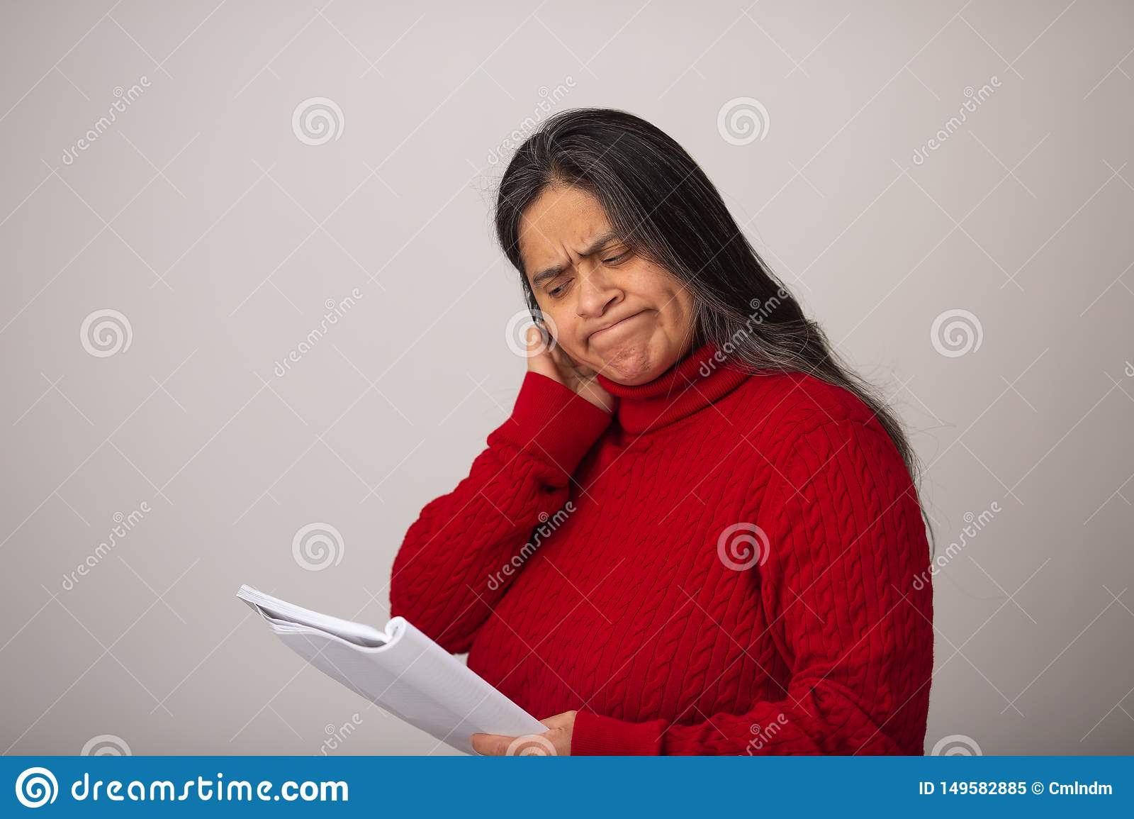 Apprehensive Hispanic Woman Looks Through Notes