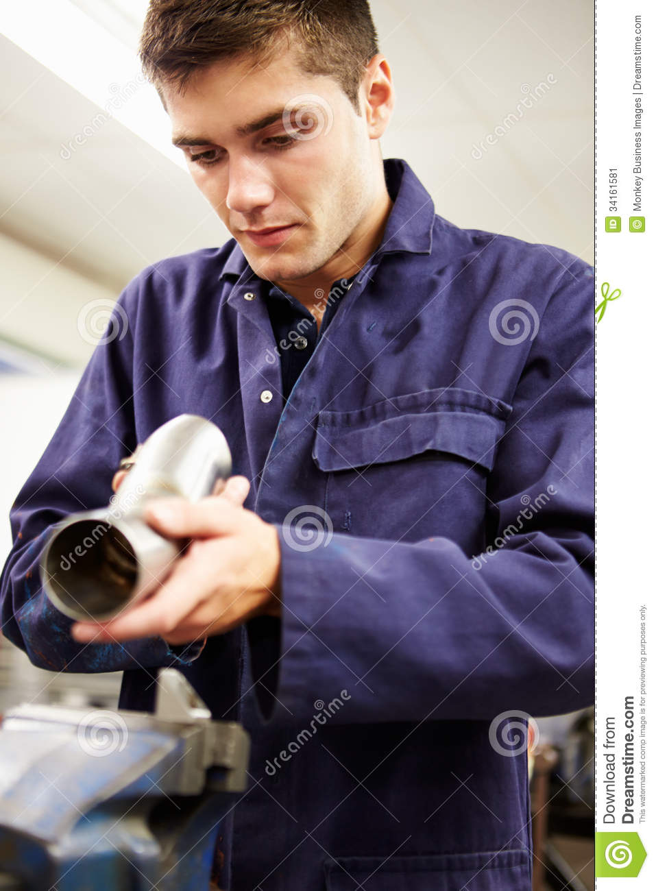 Apprentice Engineer Checking Component On Factory Floor