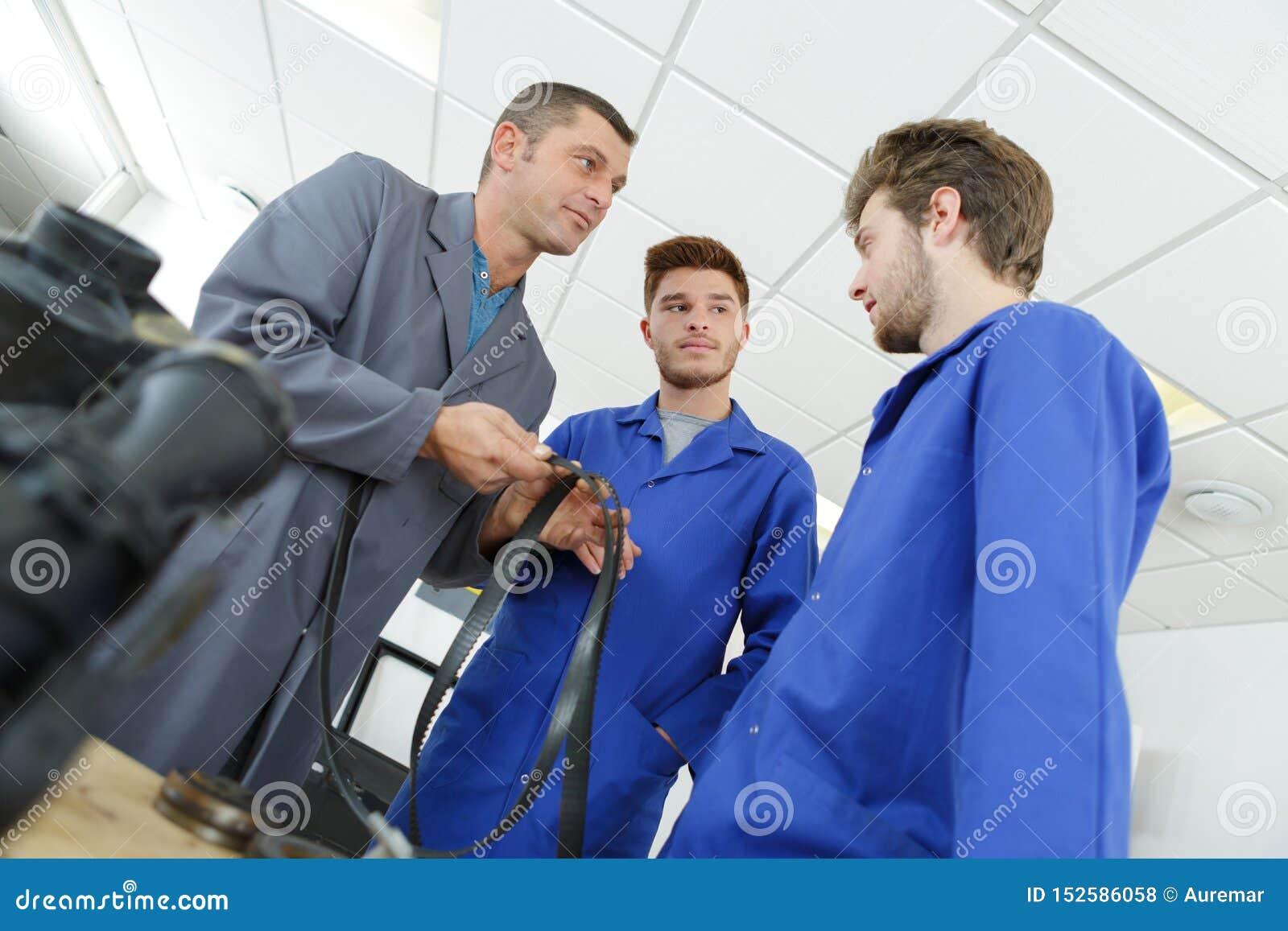 Apprentice mechanics in auto shop working on car engine
